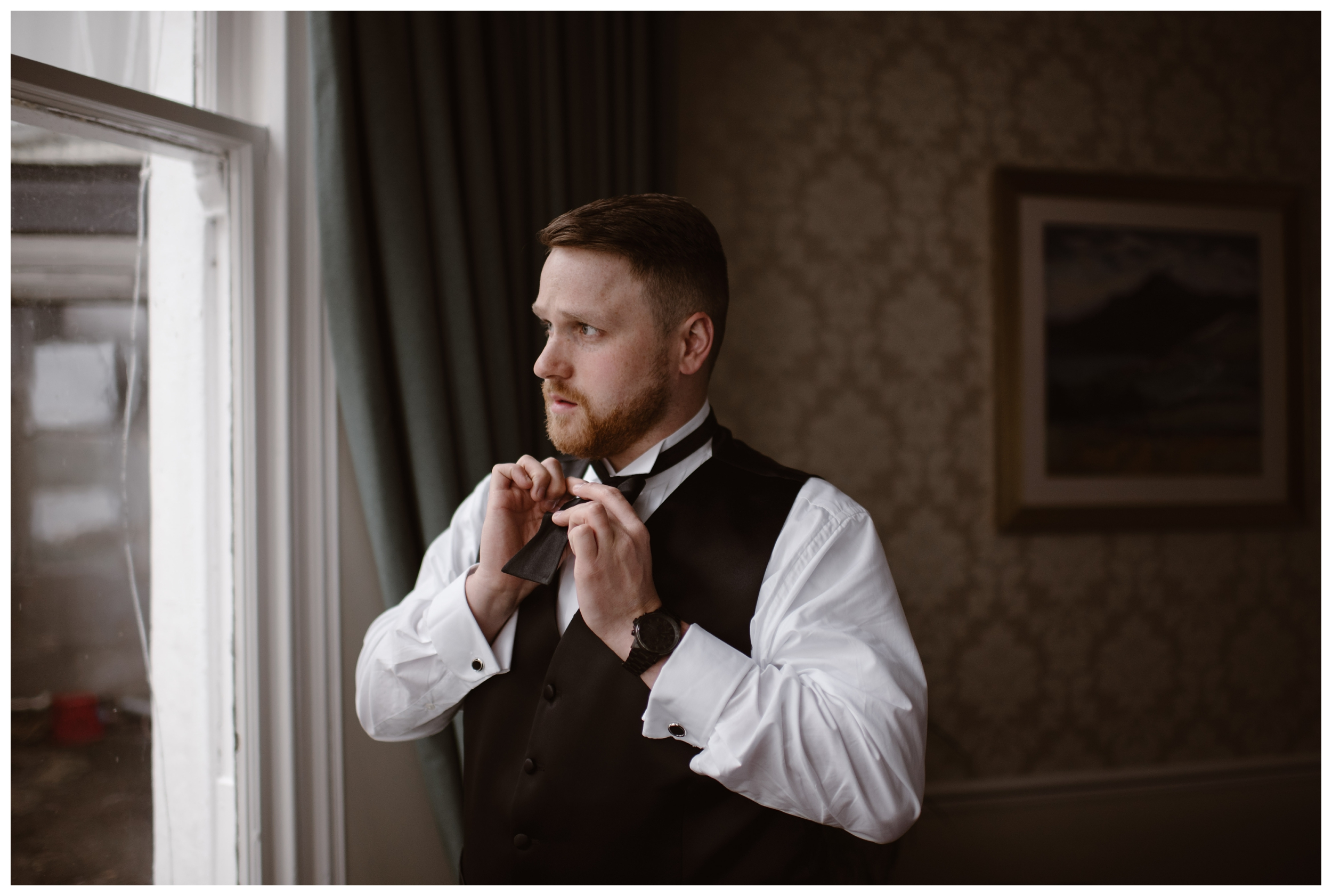 Daniel ties his tie in an old hotel outside Kilchurn Castle in Scotland before his destination elopement. Photo by Maddie Mae, Adventure Instead.