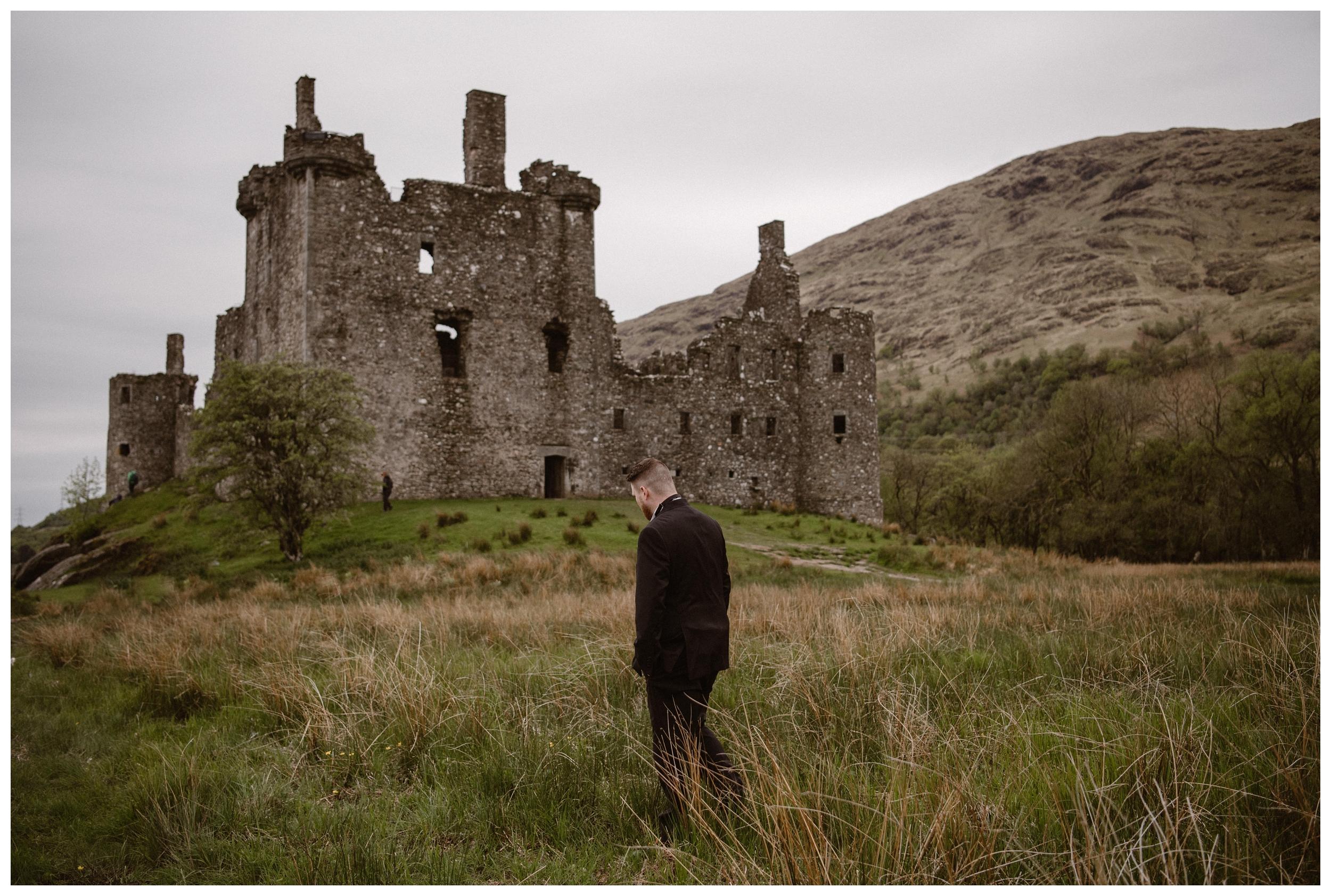 Daniel waits for his bride Elissa before their private first look at Kilchurn Castle in the Scottish Highlands. Photo by Maddie Mae, Adventure Instead.