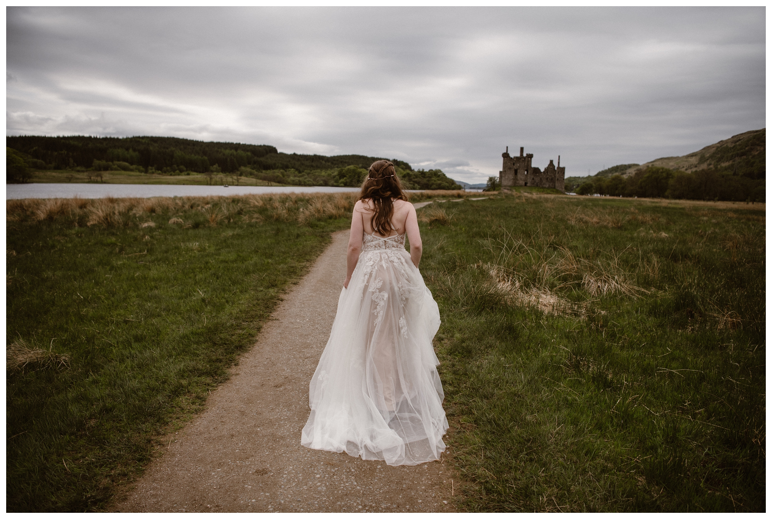 With the ruins of mid-15 century Kilchurn Castle behind her, Elissa walks on the dirt road for her first look ahead of her destination elopement ceremony. Photo by Maddie Mae, Adventure Instead.