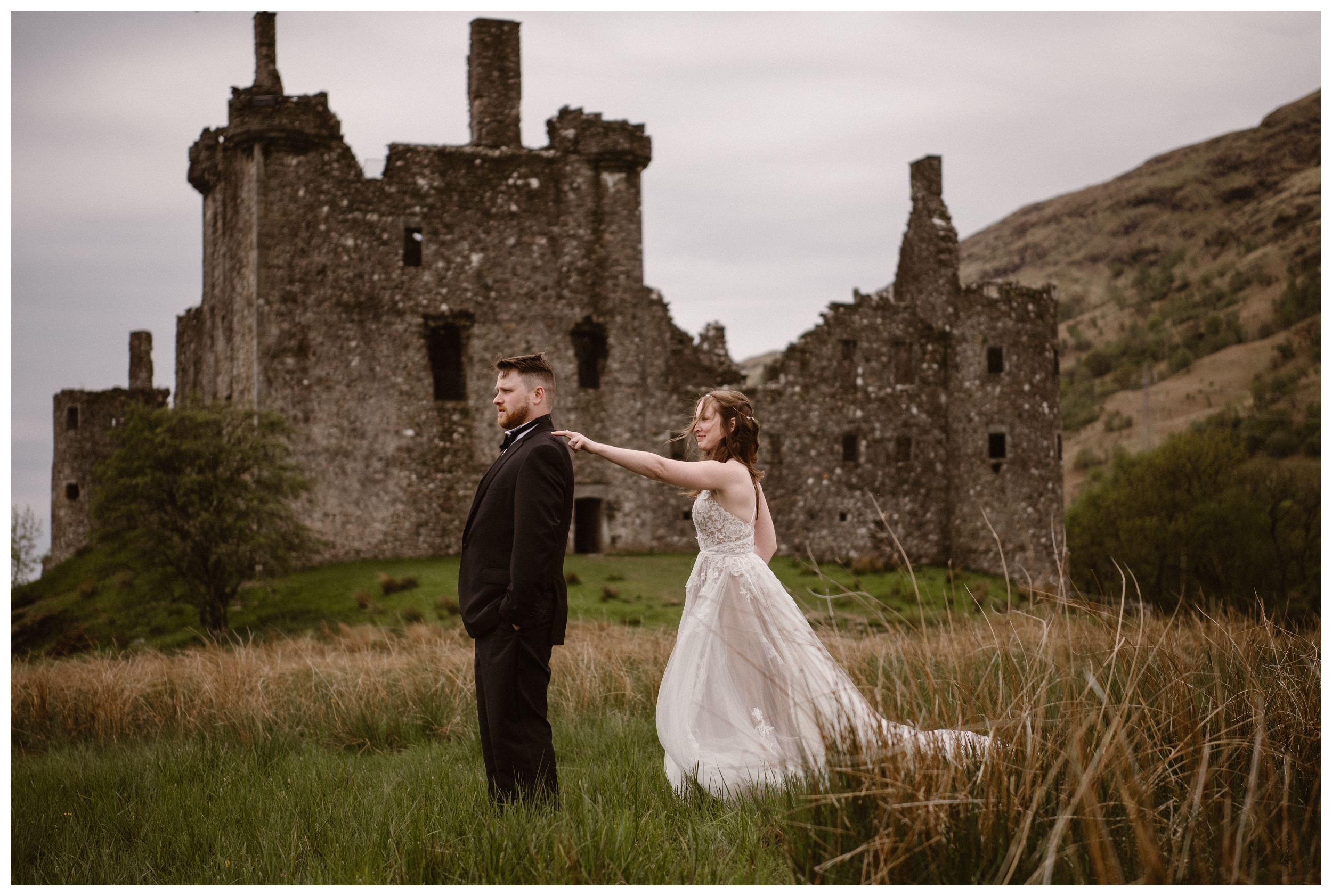 The ruins of Kilchurn Castle in Lochawe in the Scottish Highlands are behind Elissa and Daniel during their first look before their destination elopement. Photo by Maddie Mae, Adventure Instead.