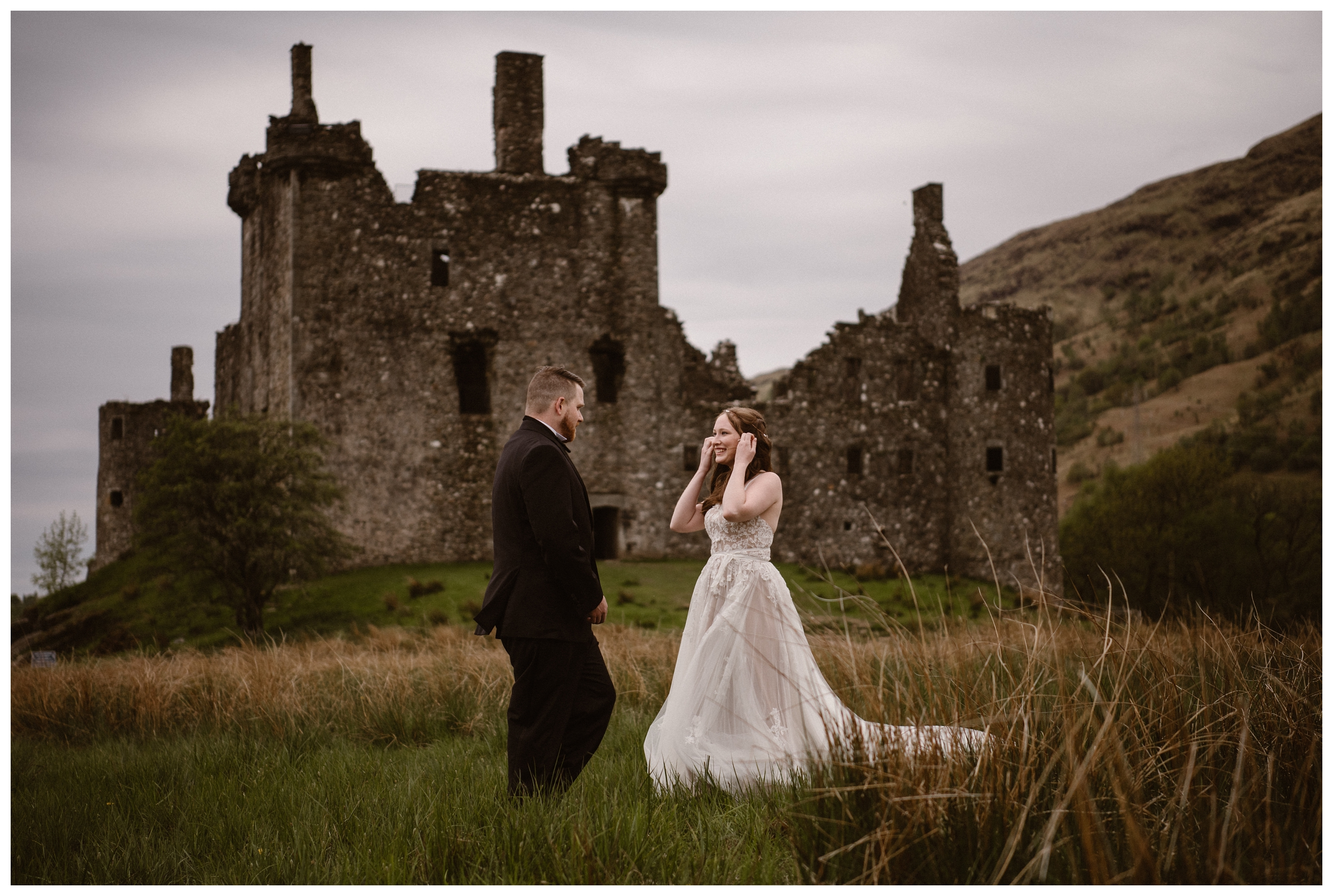 Daniel turns for his first look of his bride Elissa with the ruins of Kilchurn Castle behind them in the Scottish Highlands before their adventure destination wedding elopement. Photo by Maddie Mae, Adventure Instead.