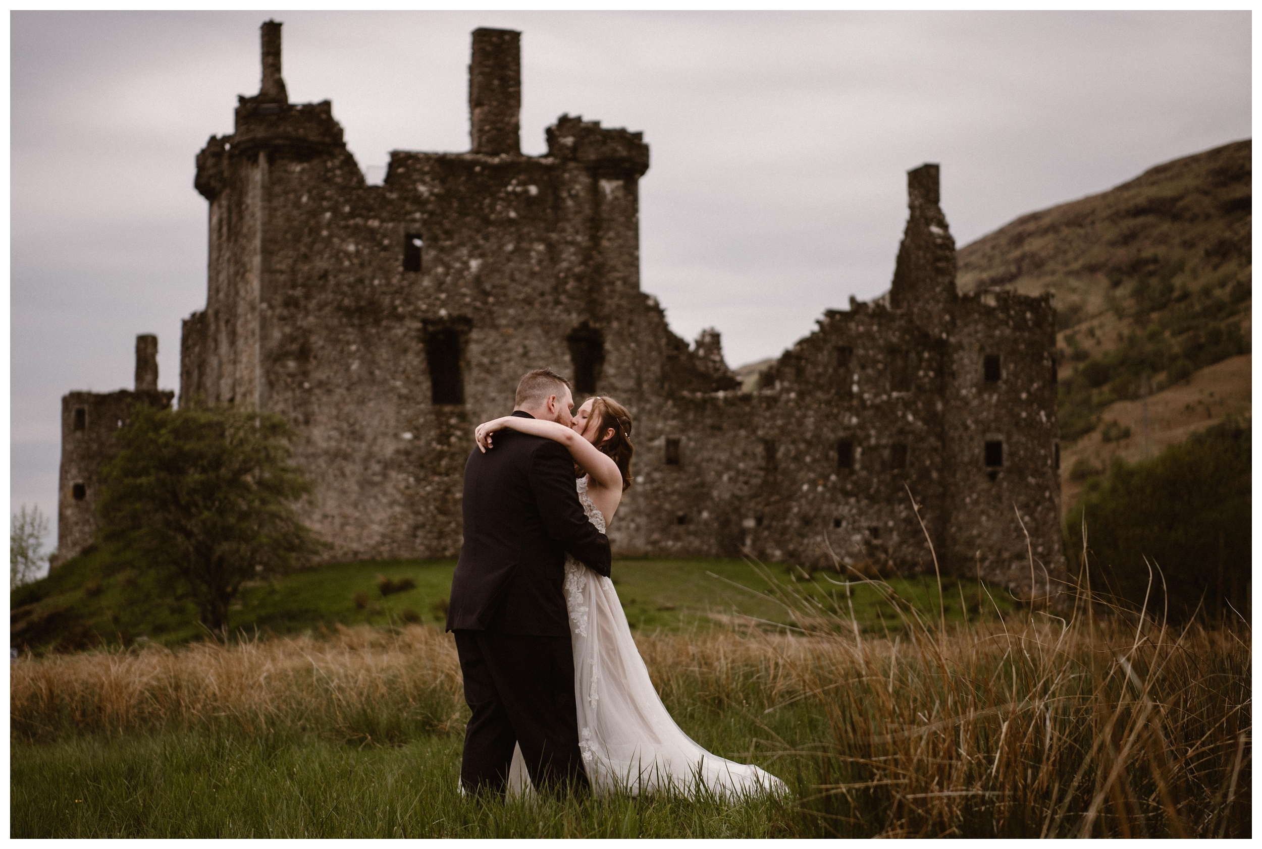 Daniel and Elissa share a kiss during their first look outside the ruins of Kilchurn Castle in Lochawe in the Scottish Highlands. Photo by Maddie Mae, Adventure Instead.