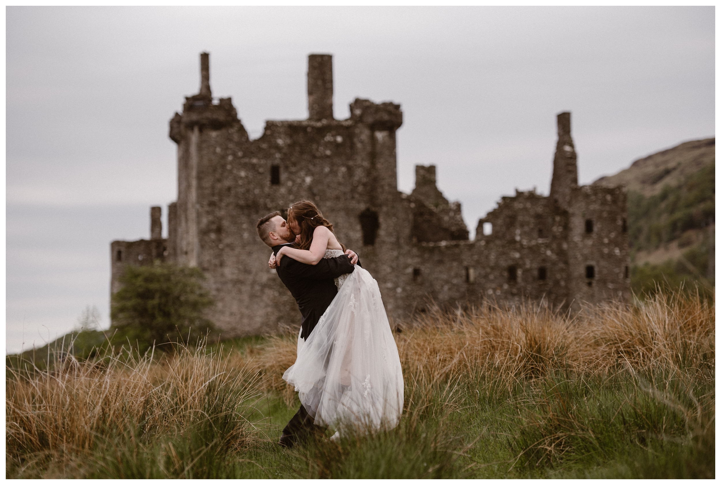 Daniel spins Elissa in the tall grass of the Scottish Highlands with the ruins of mid-15th century castle Kilchurn Castle outside Lochawe Dalmally in Scotland. Photo by Maddie Mae, Adventure Instead.