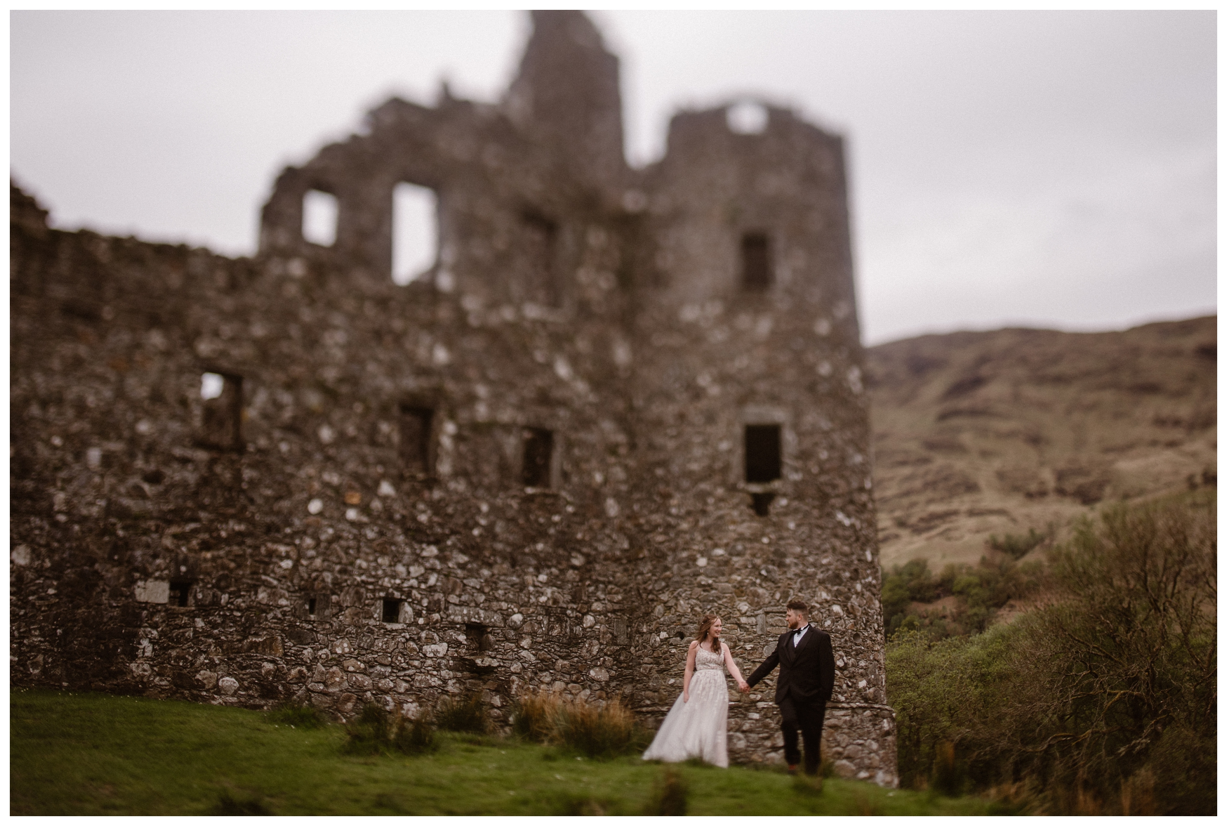 Elissa and Daniel stand at the base of Kilchurn Castle outside Loch Lomond & The Trossachs National Park in the Scottish Highlands before their destination adventure elopement. Photo by Maddie Mae, Adventure Instead.