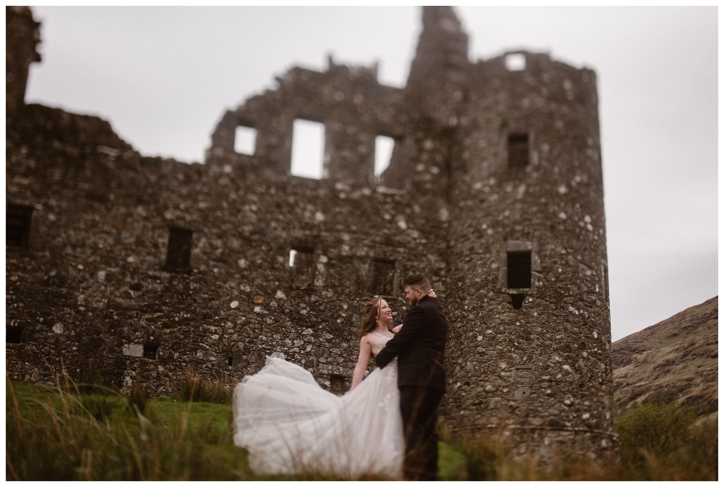 Elissa's light lace gown flows in the wind of the Scottish Highlands as she stands outside Kilchurn Castle. Photo by Maddie Mae, Adventure Instead.