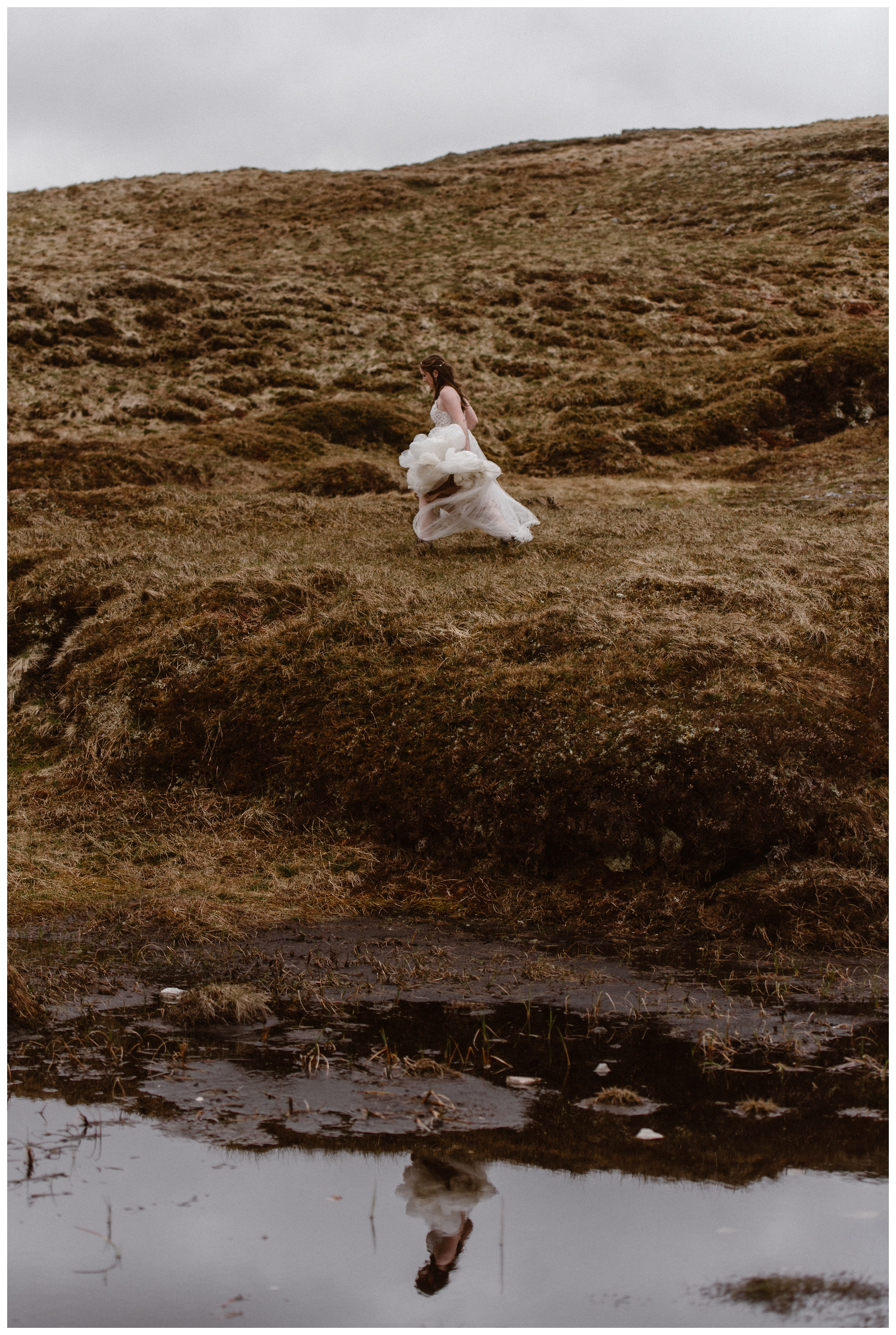 Her lace white wedding dress reflected in the boggy marshes of the Scottish Highlands, Elissa runs through the tall grass on the way to her elopement ceremony. Photo by Maddie Mae, Adventure Instead.