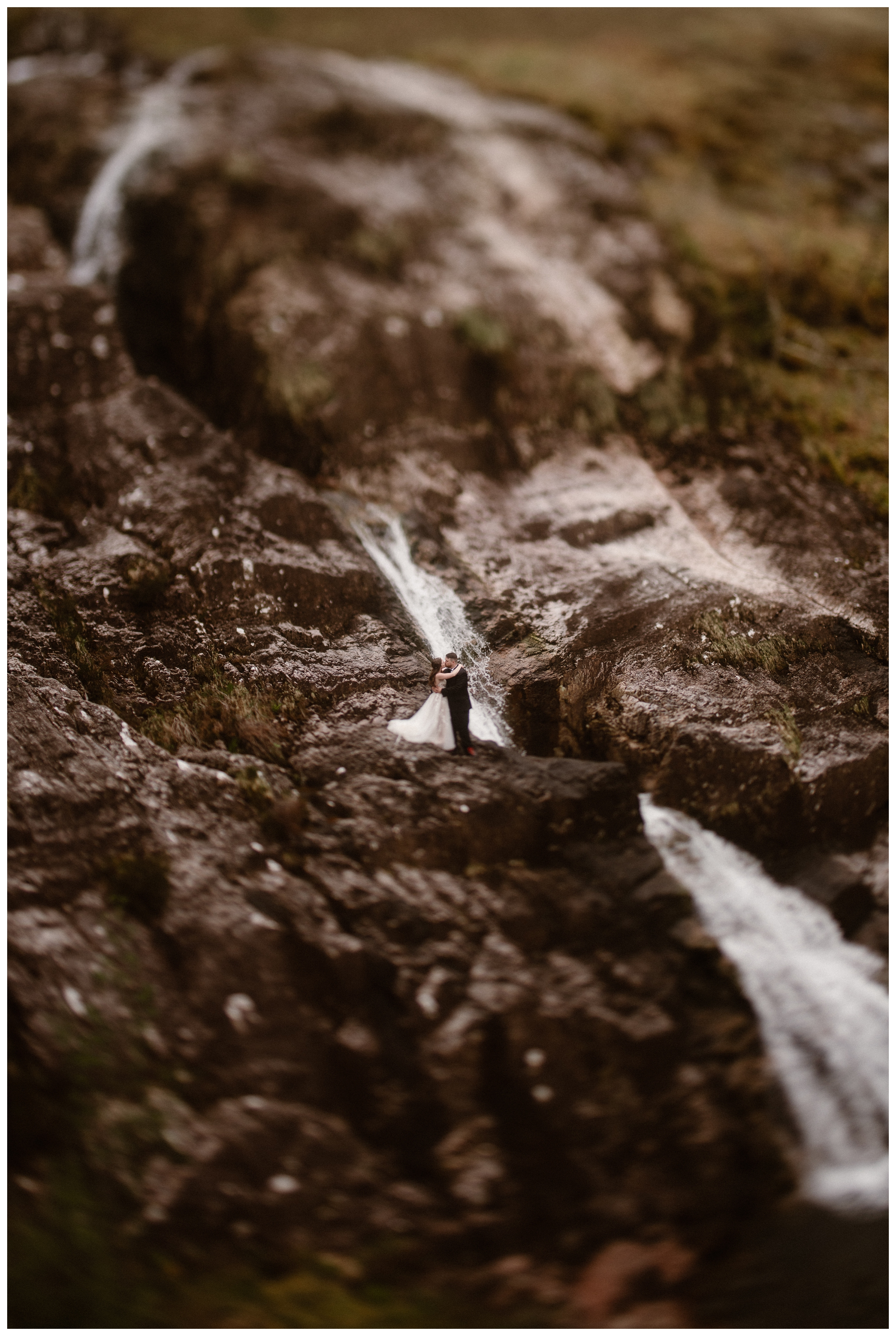 Elissa and Daniel are surrounded by a waterfall flowing through the Scottish Highlands outside Glencoe, Scotland. Photo by Maddie Mae, Adventure Instead.