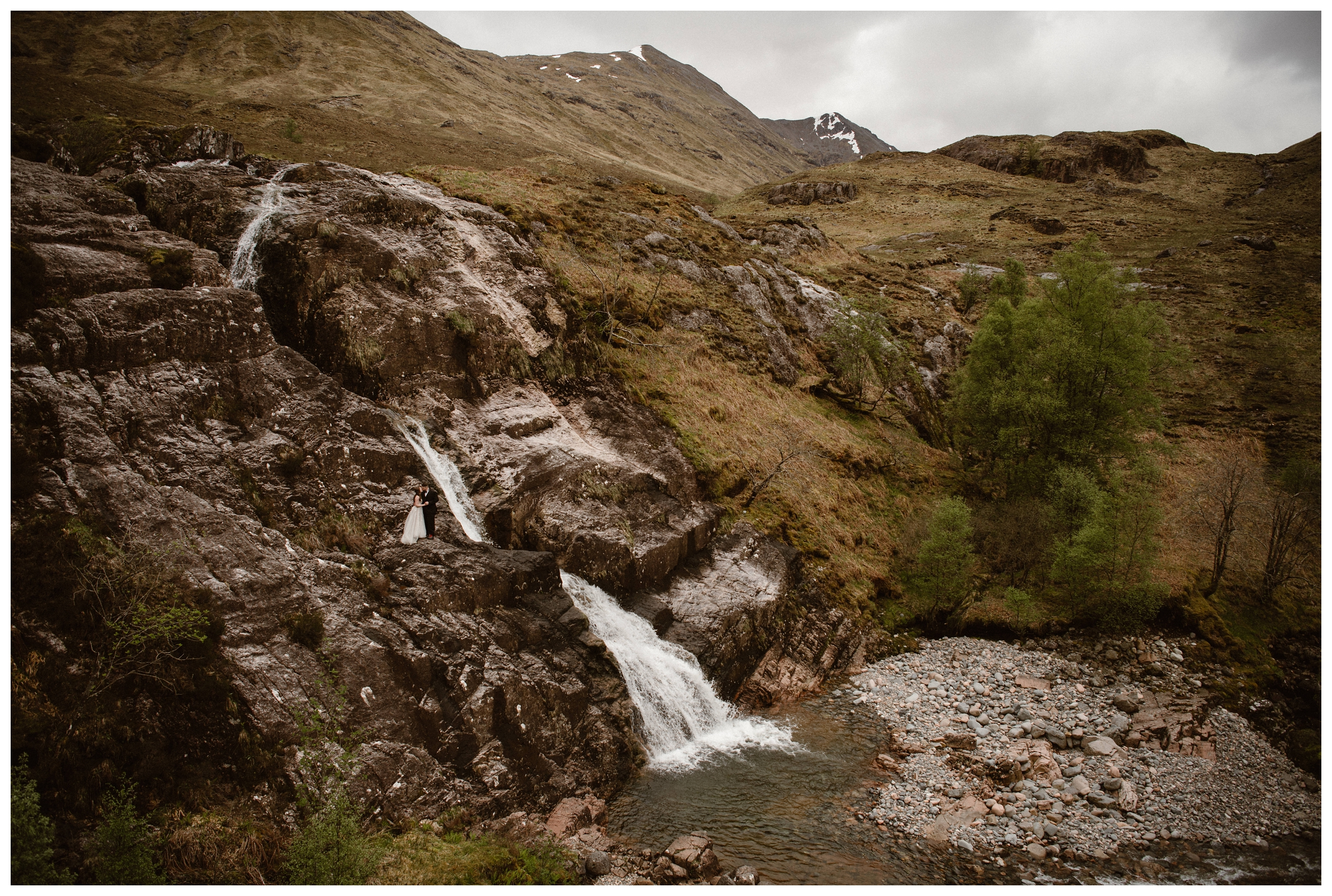 Elissa and Daniel are dwarfed by the rocky landscape of the Scottish Highland bogs and marshes outside Glencoe, Scotland following their self solemnizing elopement ceremony. Photo by Maddie Mae, Adventure Instead.