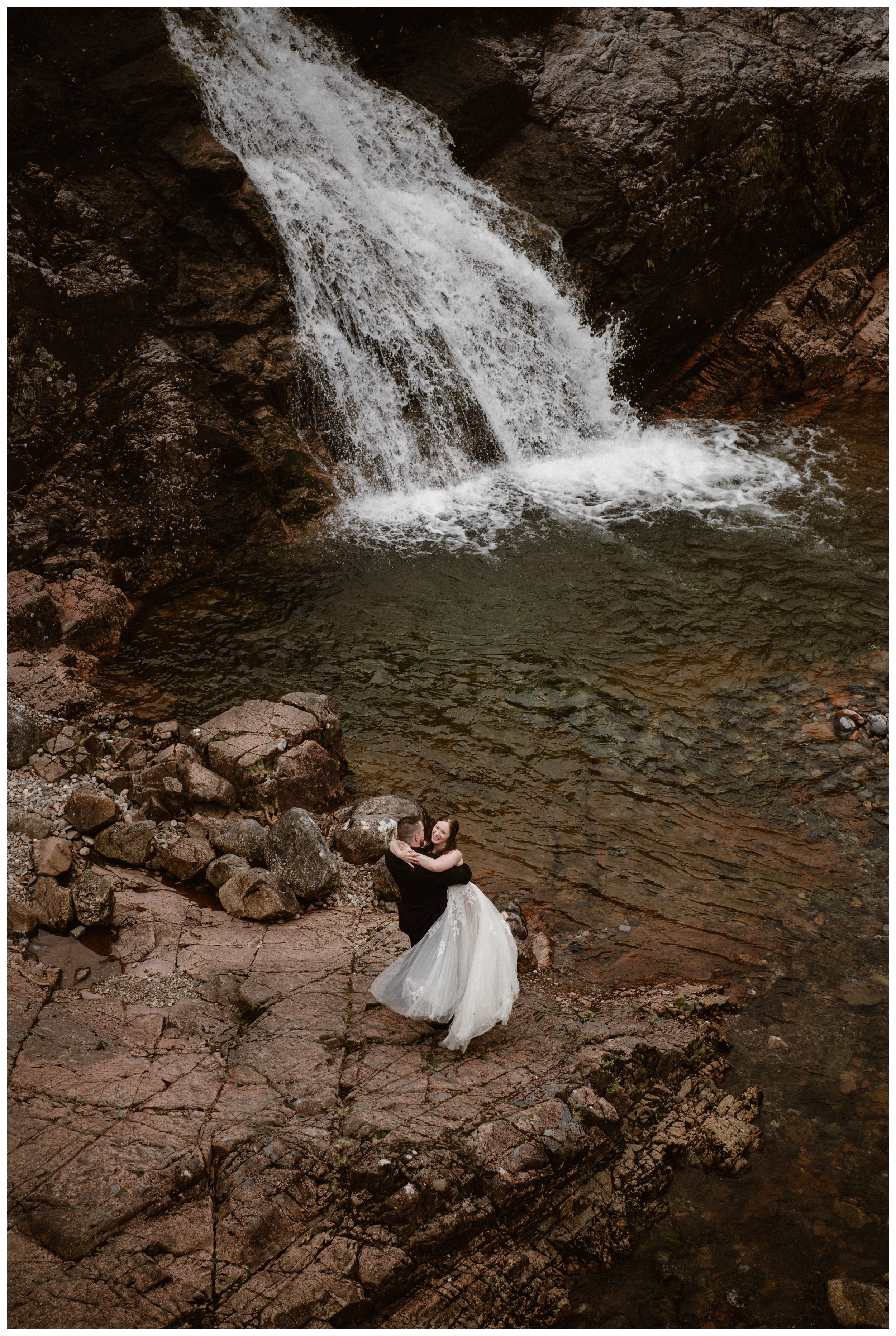 Daniel and Elissa celebrate their recent self solemnizing adventure elopement ceremony in the Scottish Highlands at the base of a waterfall. Photo by Maddie Mae, Adventure Instead.