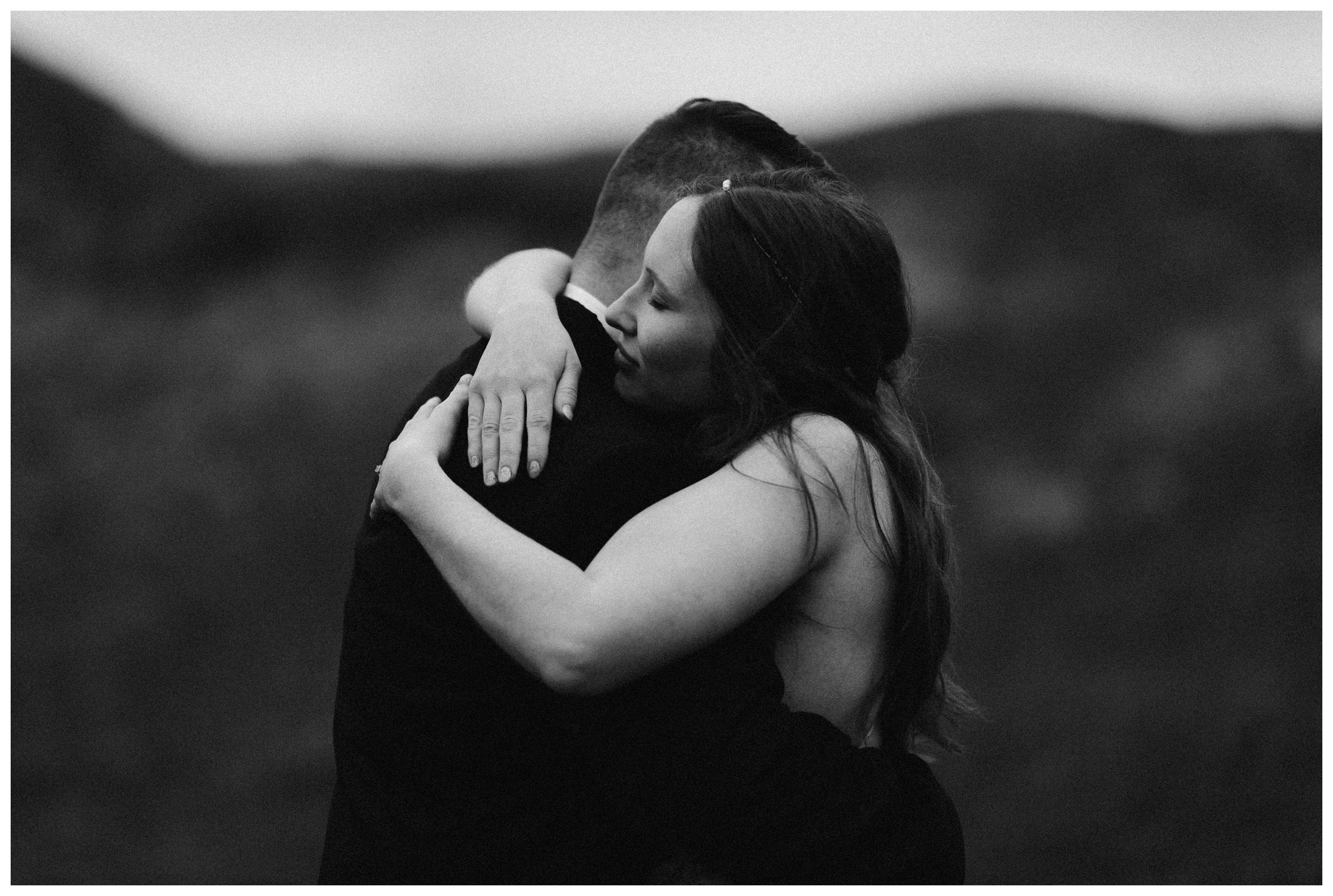 Elissa and Daniel share an embrace in the Scottish Highlands following their private destination adventure elopement ceremony outside Glencoe, Scotland. Photo by Maddie Mae, Adventure Instead.
