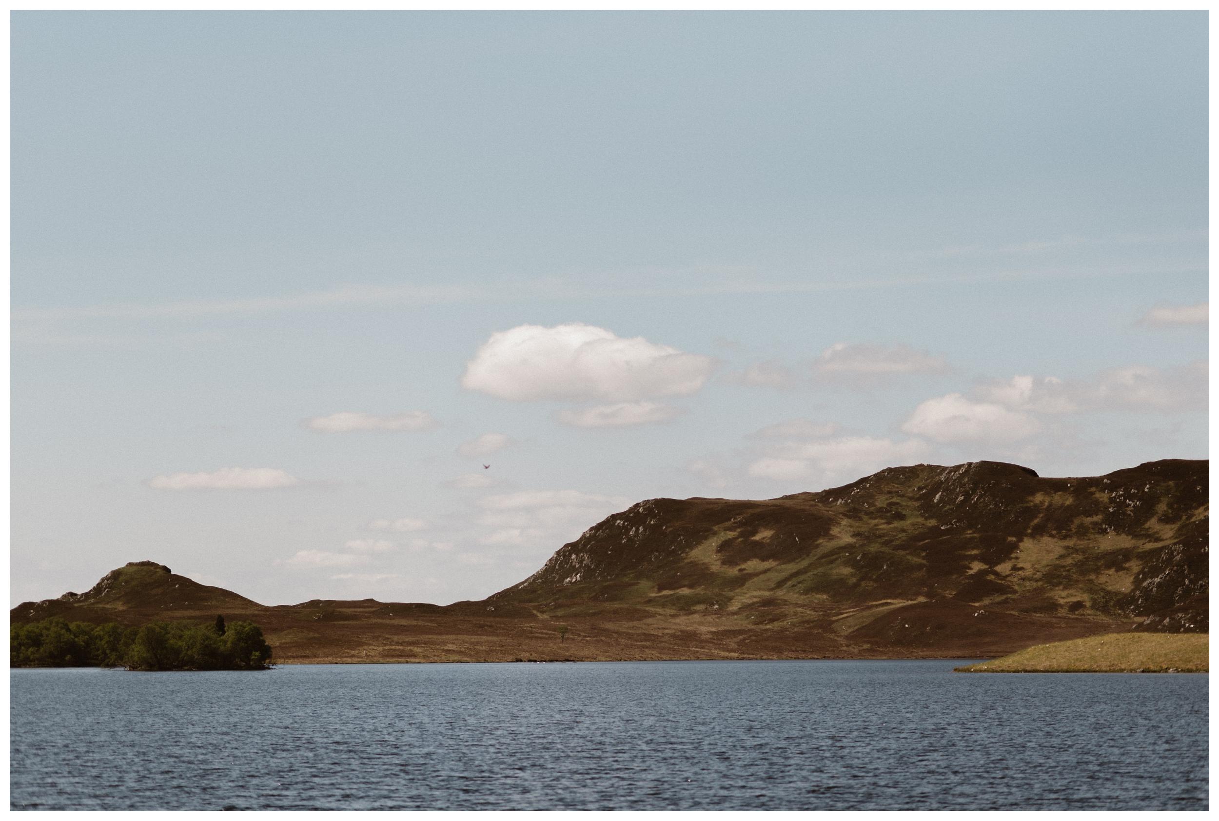 The hills surrounding Loch Ness in the Scottish Highlands are visible on a surprisingly cloudless day in May for Elissa and Daniel's adventure elopement. Photo by Maddie Mae, Adventure Instead.