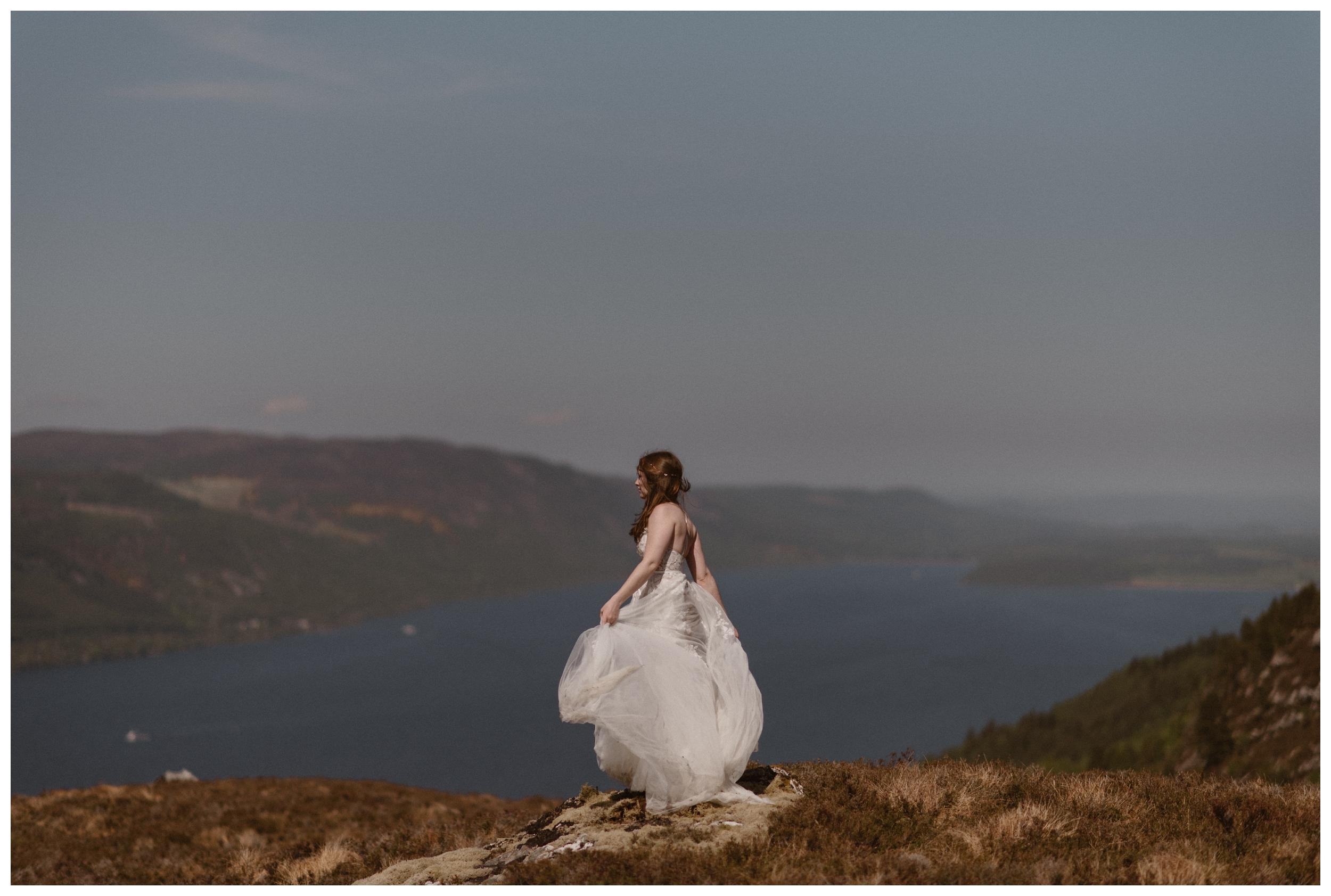 Elissa stands in her wedding dress on a ridge overlooking Loch Ness in the Scottish Highlands. Photo by Maddie Mae, Adventure Instead.