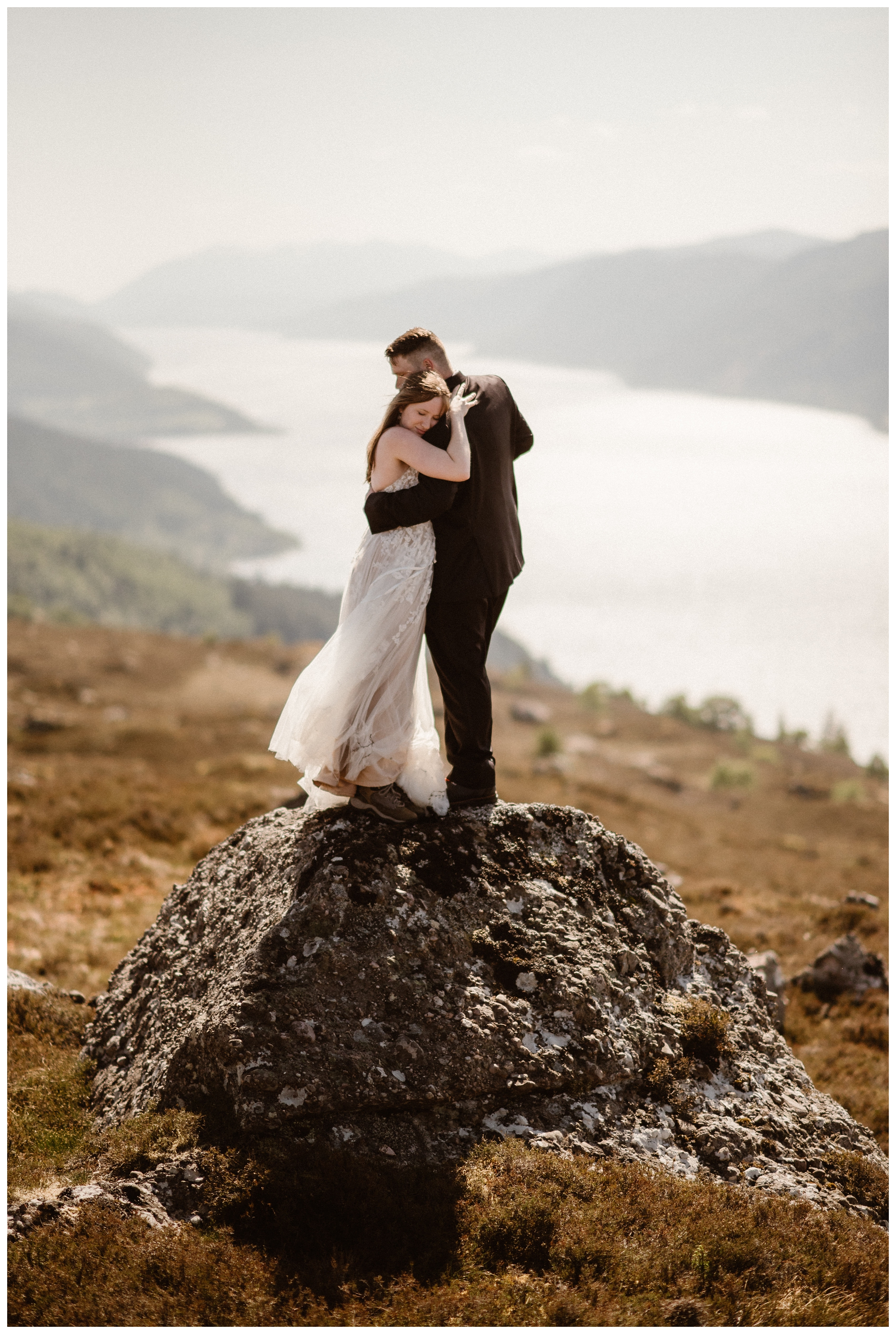 Elissa and Daniel stand on a rock overlooking the north shores of Loch Ness in the Scottish Highlands. We could nearly make out Urquhart Castle during the photos for their destination elopement. Photo by Maddie Mae, Adventure Instead.