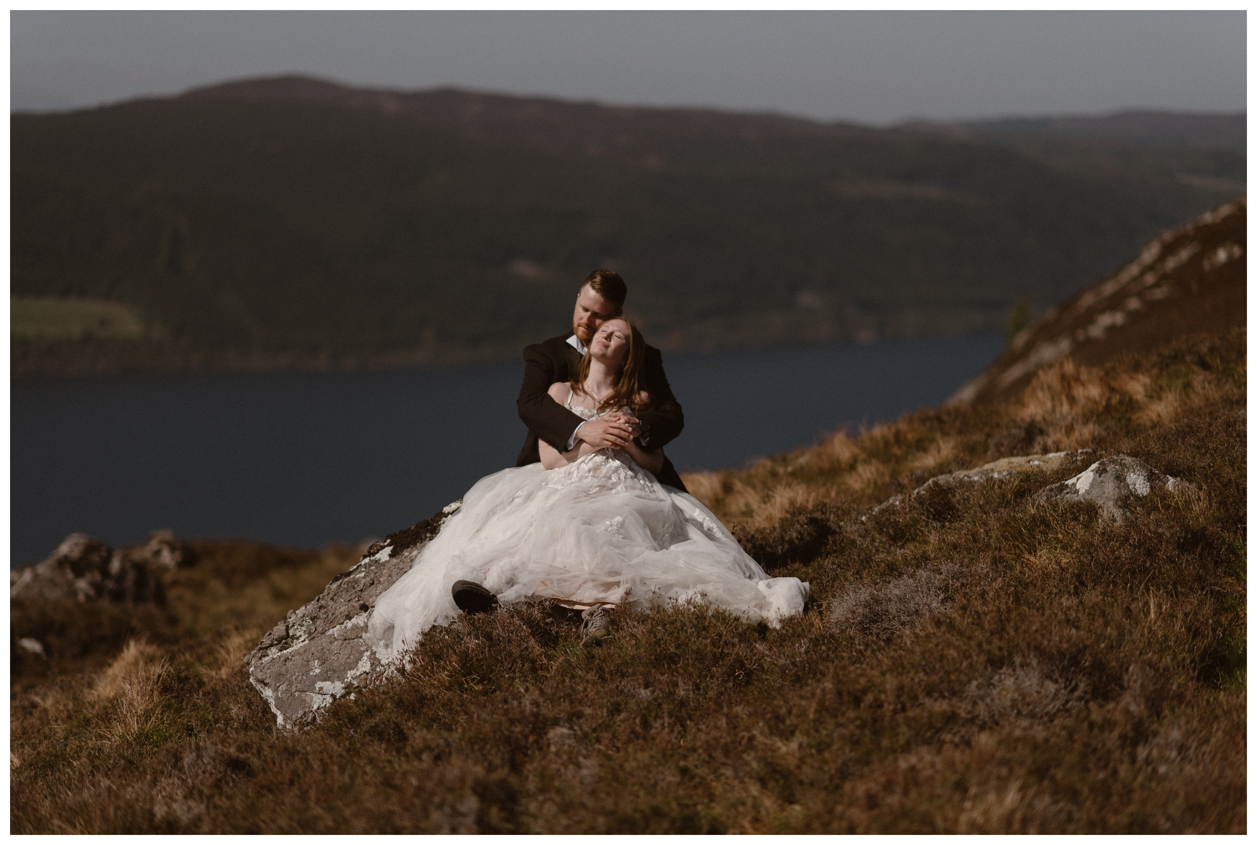 Elissa and Daniel share an embrace on a rock on the shores of Loch Ness in the Scottish Highlands following their destination elopement adventure. Photo by Maddie Mae, Adventure Instead.