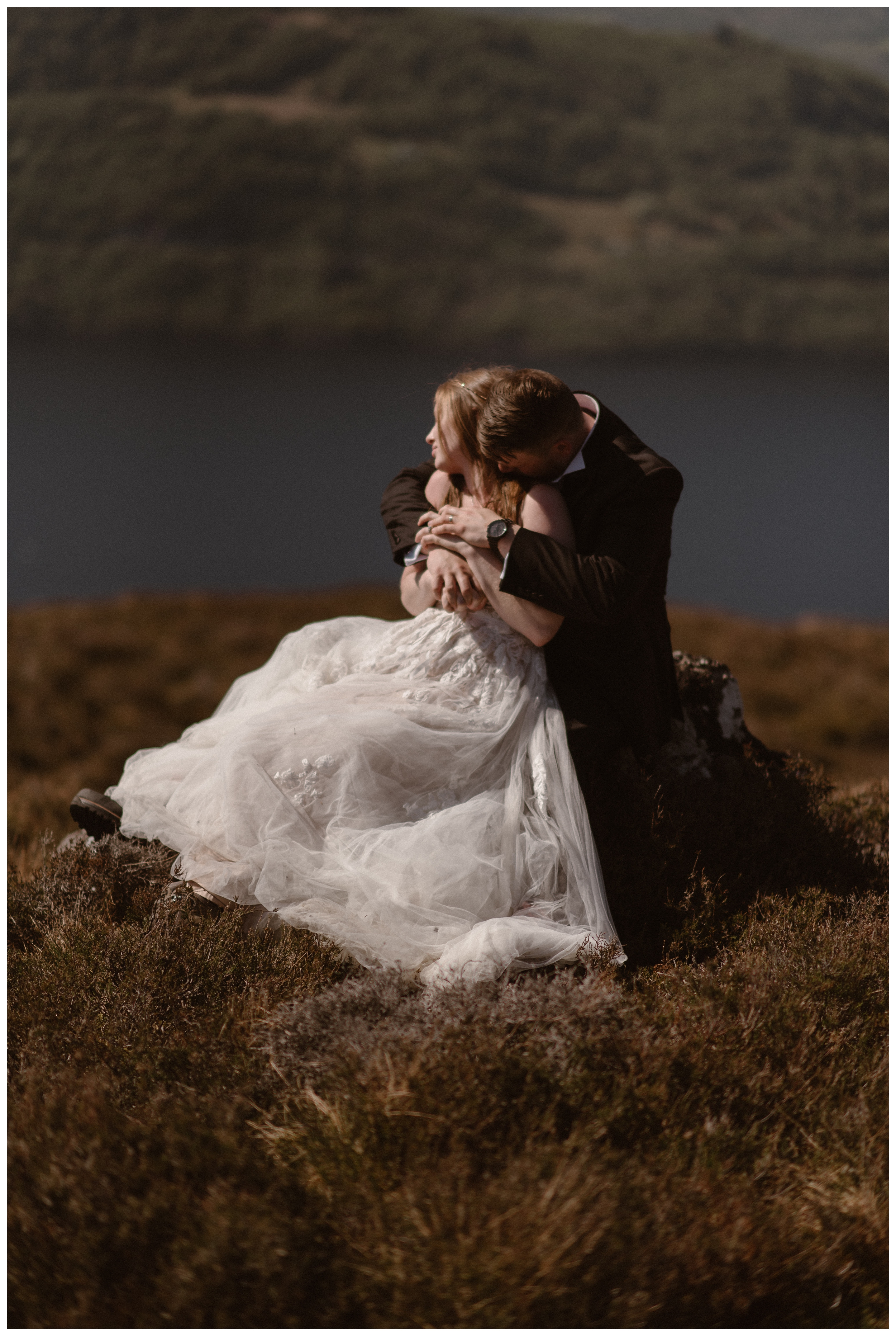 We helped Elissa and Daniel plan their destination elopement in the Scottish Highlands, even though they had never been. They embrace on a rock on the shores of Loch Ness in Scotland following their ceremony. Photo by Maddie Mae, Adventure Instead.