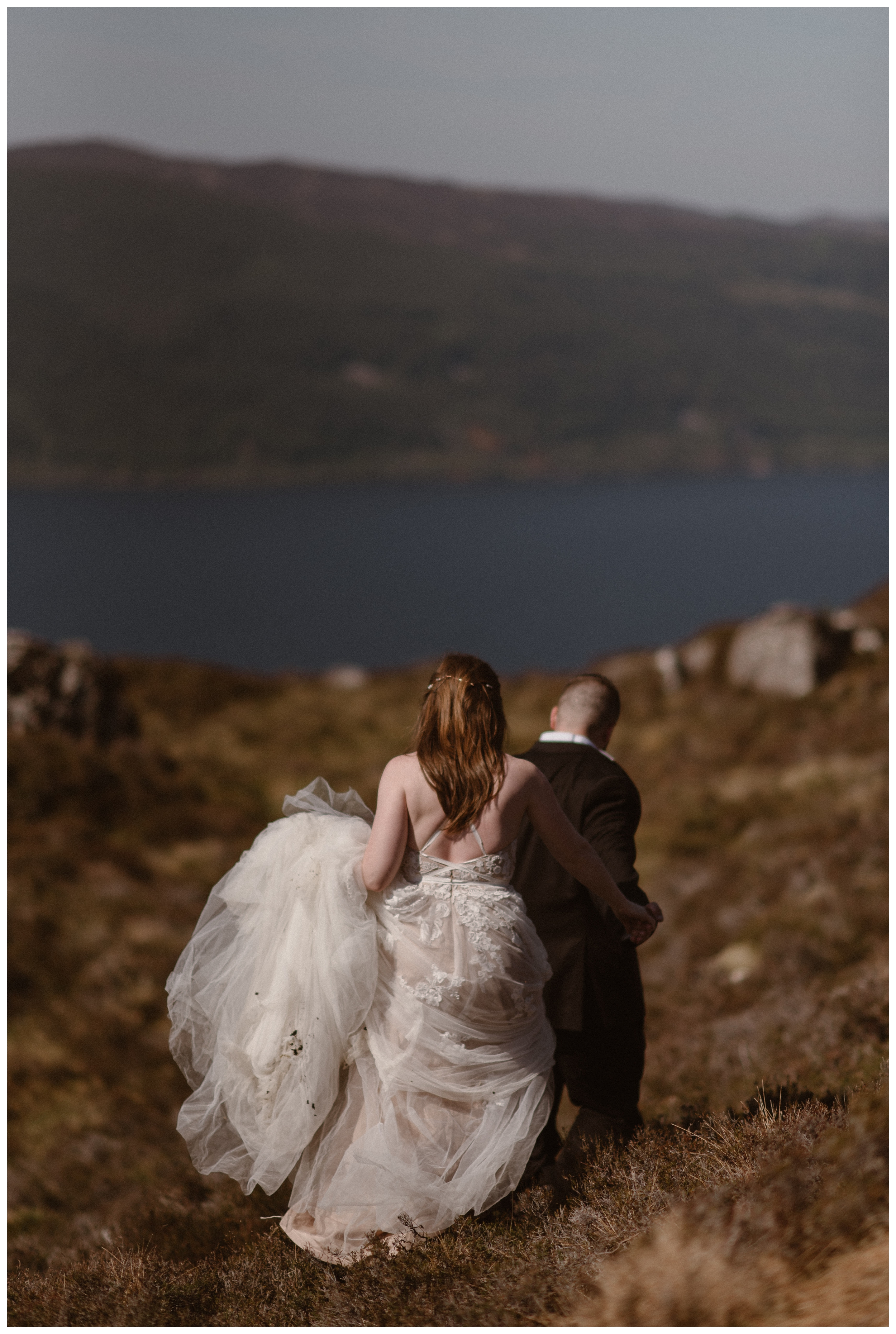 Elissa and Daniel hiked, wandered, and explored the shores of Loch ness in the Scottish Highlands in their wedding day attire following their Glencoe, Scotland elopement. Photo by Maddie Mae, Adventure Instead.