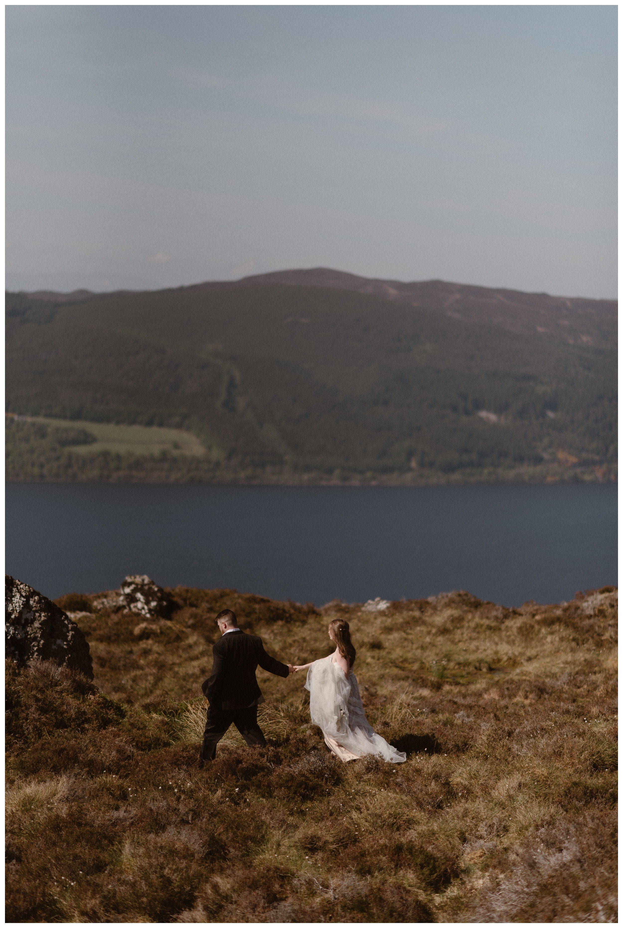 On the shores of Loch Ness in the Scottish Highlands, Elissa and Daniel walk through the grass together following their destination adventure elopement. Photo by Maddie Mae, Adventure Instead.