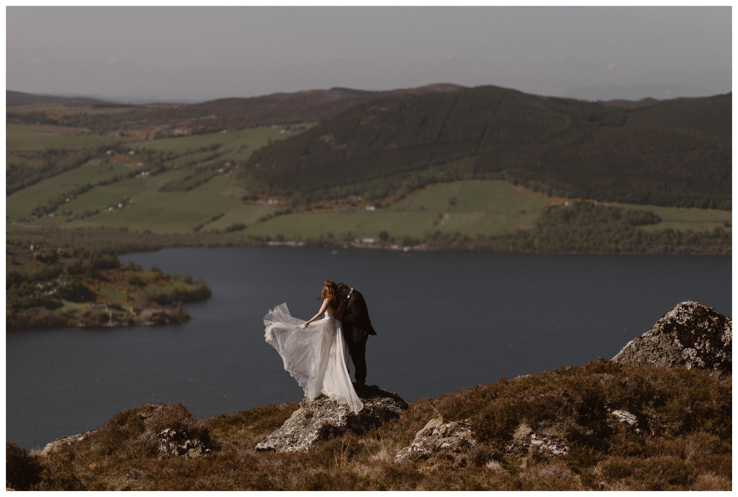 The rolling hills of the Scottish Highlands and the ruins of Urquhart Castle are behind Elissa and Daniel as they embrace following their destination wedding elopement. Photo by Maddie Mae, Adventure Instead.