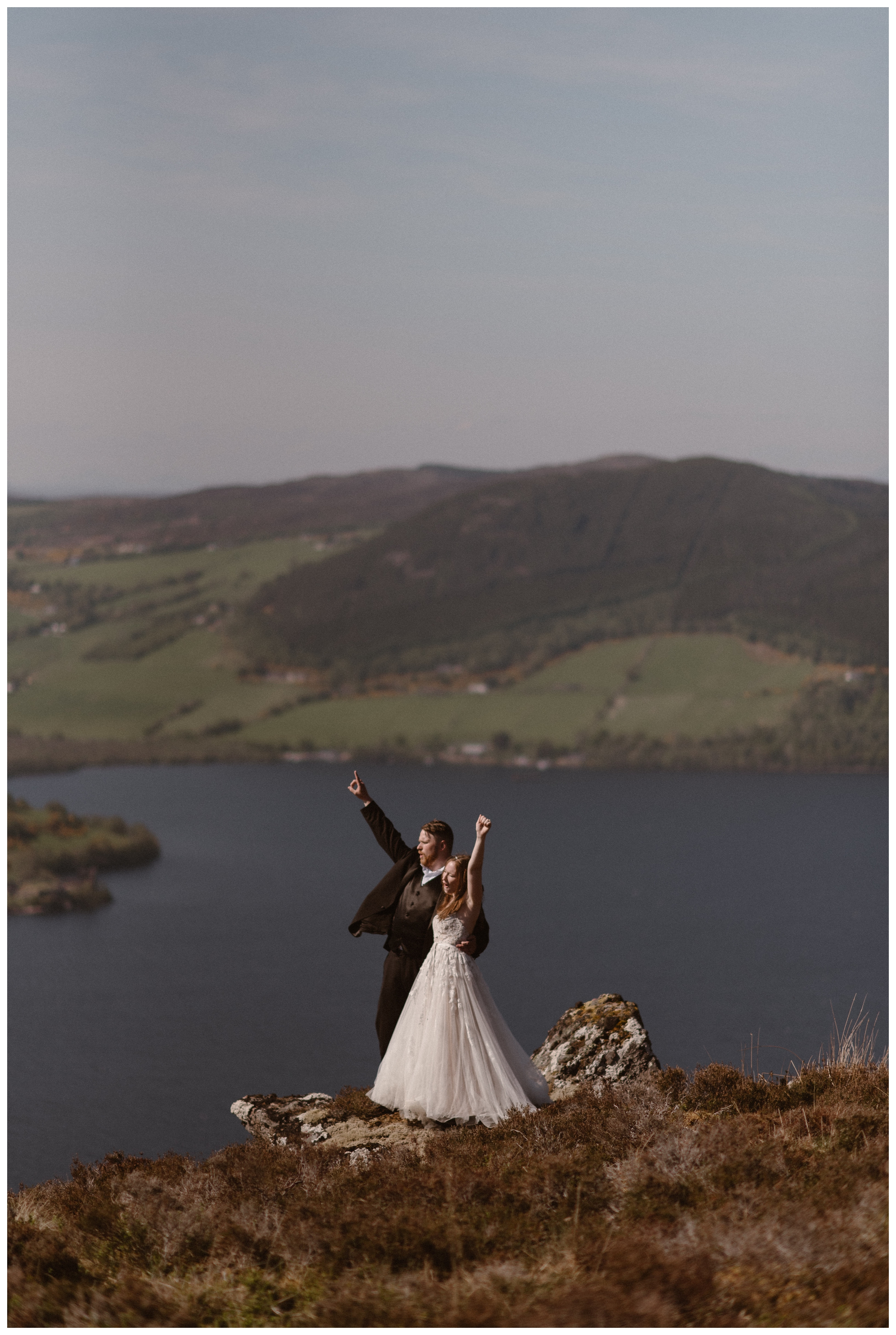 Elissa and Daniel let out a cheer on the shores of Loch Ness following their adventure destination elopement ceremony in the Scottish Highlands. The weather in Scotland was surprisingly clear for late May. Photo by Maddie Mae, Adventure Instead.