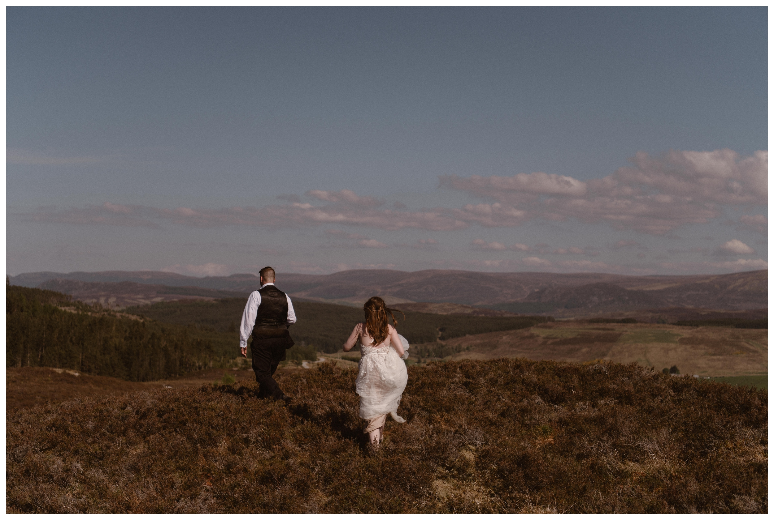 The rolling Scottish Highland hills before them, Elissa and Daniel explore together following their destination elopement. Photo by Maddie Mae, Adventure Instead.