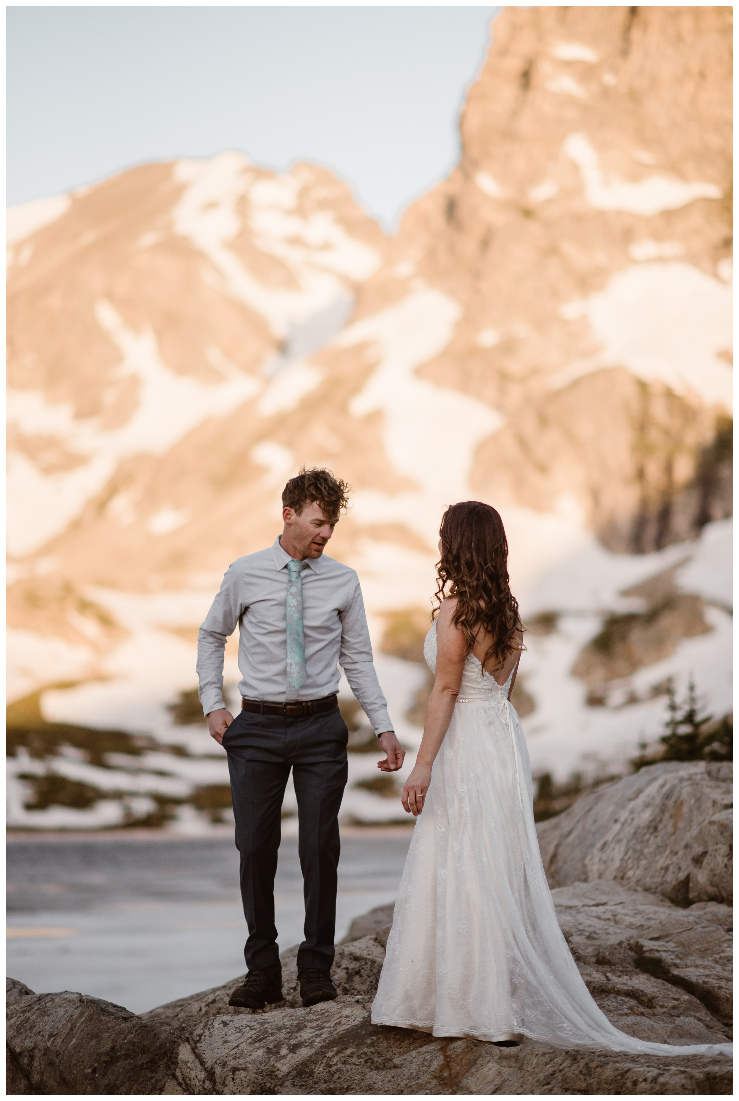 Matt and Karen's first look for their adventure hiking elopement outside Nederland, Colorado was beautiful with mountains glowing pink with alpenglow behind them. Photo by Adventure Instead, Maddie Mae.
