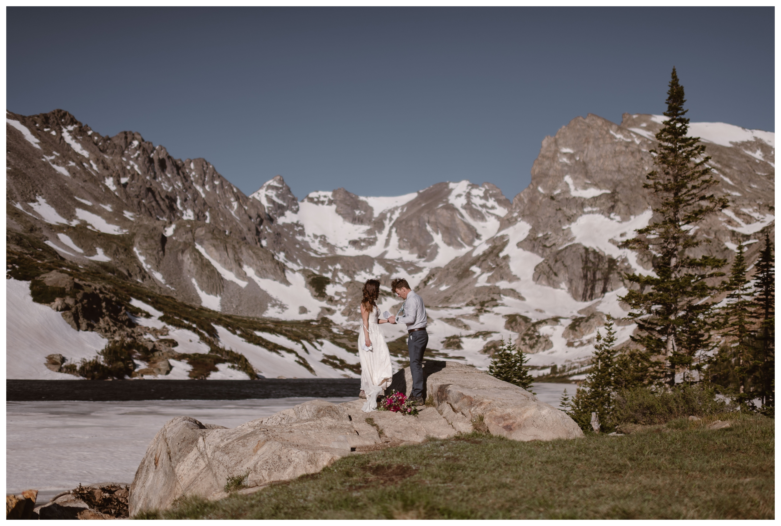 Karen and Matt say their vows during their self solemnizing adventure elopement ceremony with snowy mountain peaks behind them. Photo by Adventure Instead, Maddie Mae.