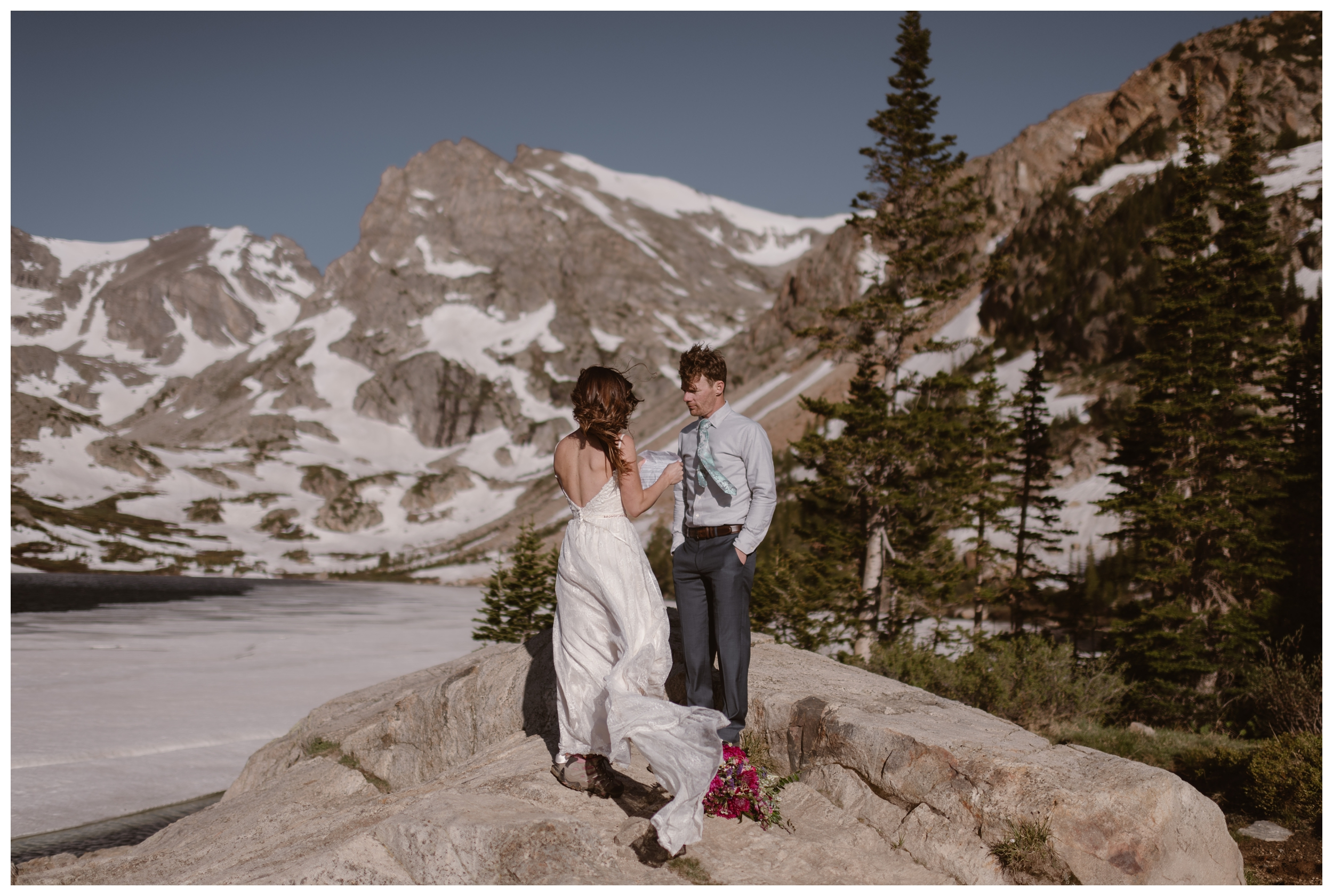 As the high alpine wind blows around them, Karen and Matt read their vows during their adventure elopement ceremony at the top of Lake Isabelle, above Brainard Lake in Nederland, Colorado. Photo by Adventure Instead, Maddie Mae.