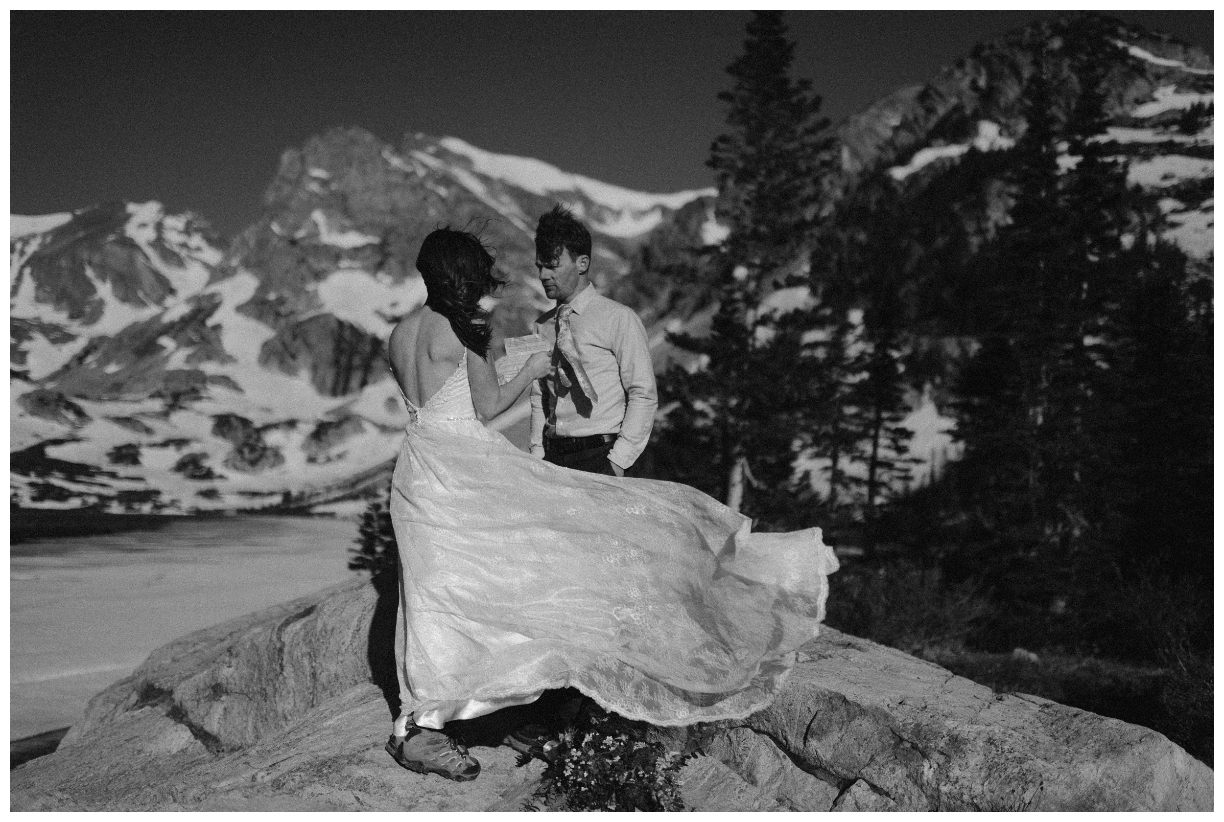 Karen's dress blows as she reads her vows during their self solemnizing elopement wedding ceremony at the top of Lake Isabelle in Nederland, Colorado. Photo by Adventure Instead, Maddie Mae.