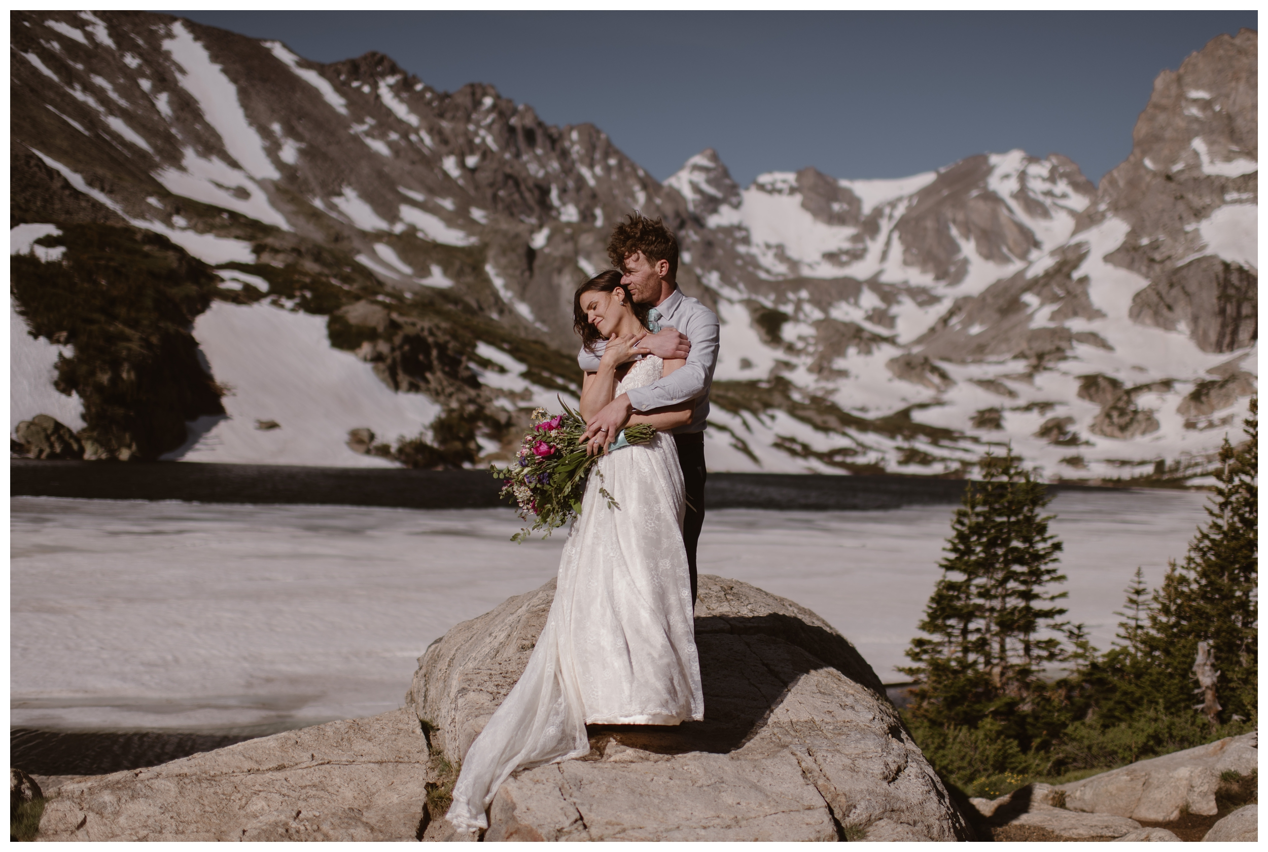 Snowy mountain peaks of Nederland, Colorado behind them, Karen and Matt embrace after their high alpine lake elopement ceremony. Photo by Adventure Instead, Maddie Mae.