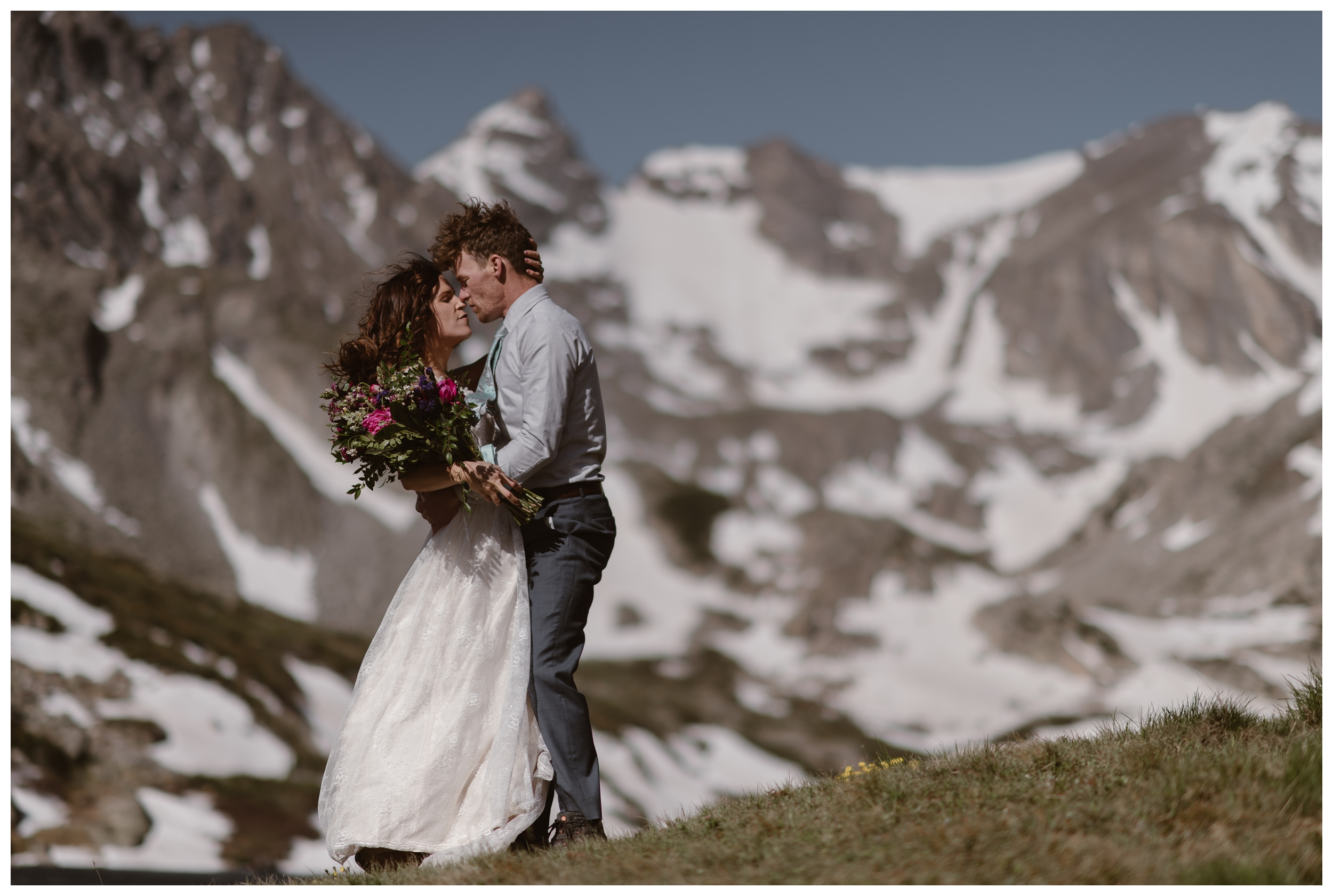 The snowy mountains of early spring and summer in the Colorado Rocky Mountains are behind Karen and Matt as they embrace following their high alpine lake elopement ceremony. Photo by Adventure Instead, Maddie Mae.