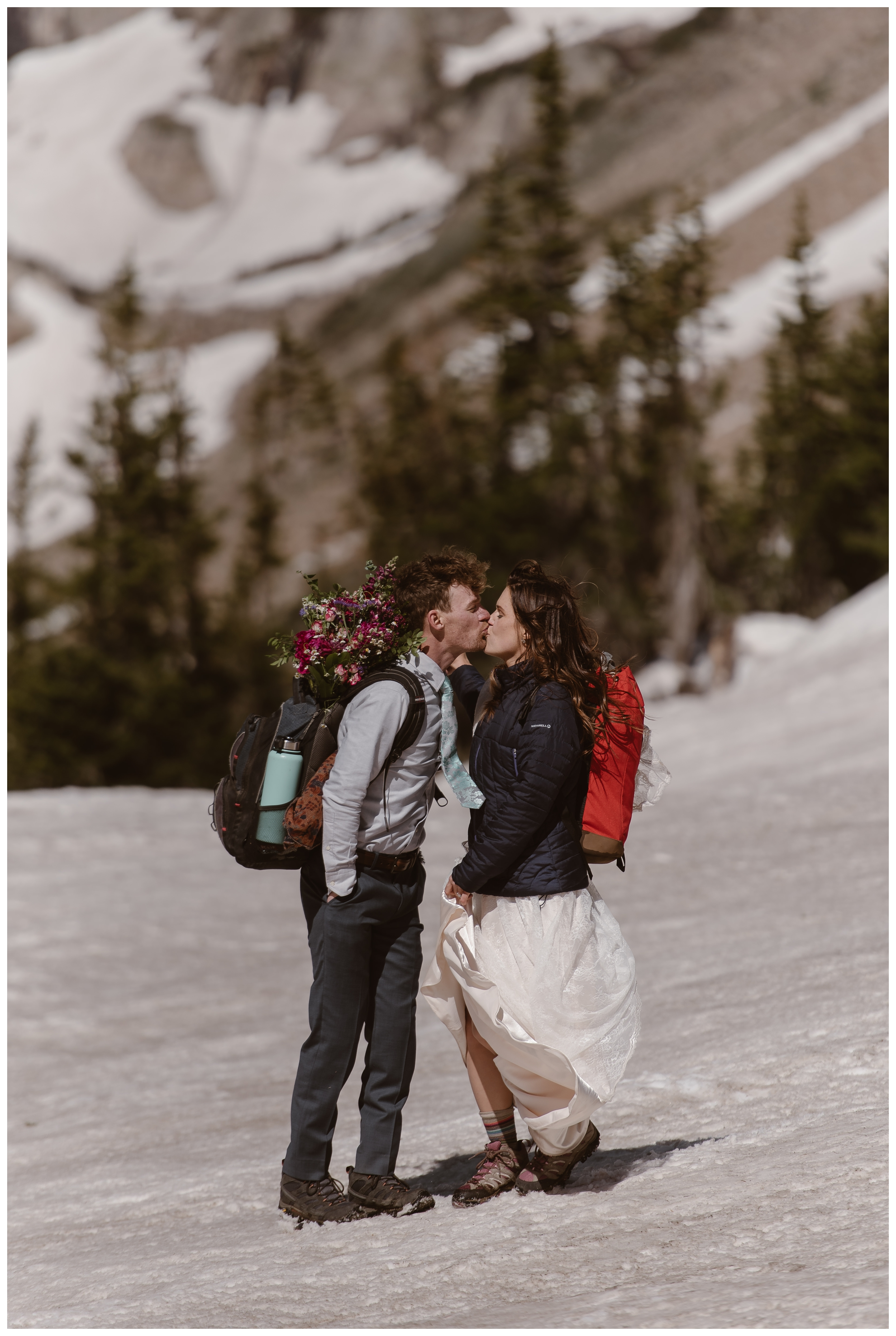 Karen and Matt kiss in a snow field at the top of Lake Isabelle, in Nederland, Colorado following their high alpine lake elopement ceremony. Photo by Adventure Instead, Maddie Mae.