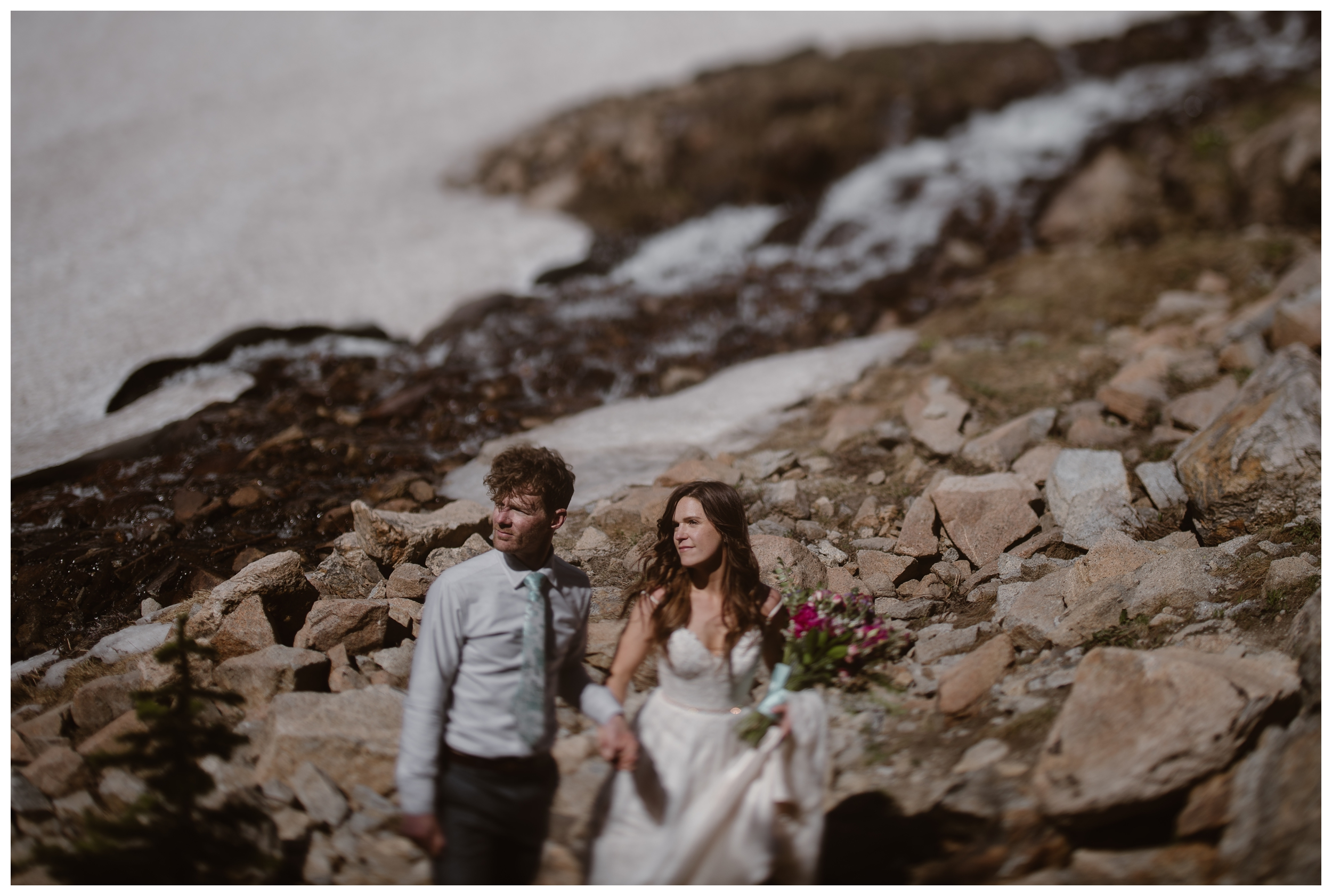 The rocky shores of Lake Isabelle, a high alpine lake outside Nederland, Colorado, are behind Karen and Matt as they hike and explore following their adventure elopement ceremony. Photo by Adventure Instead, Maddie Mae.