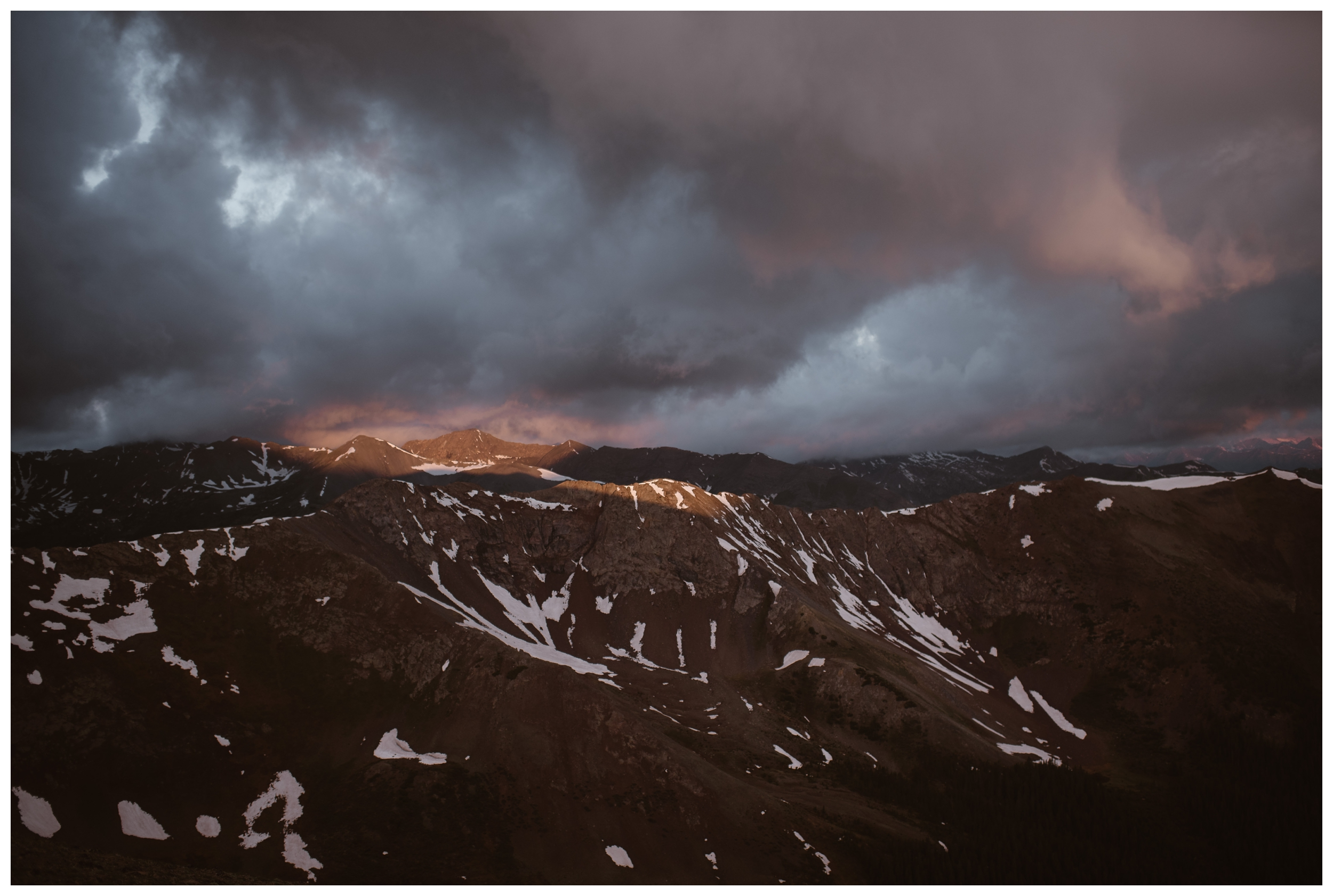 Dark clouds give way to the pink glow of sunrise on the jagged peaks above Independence Pass. Photo by Maddie Mae, Adventure Instead.