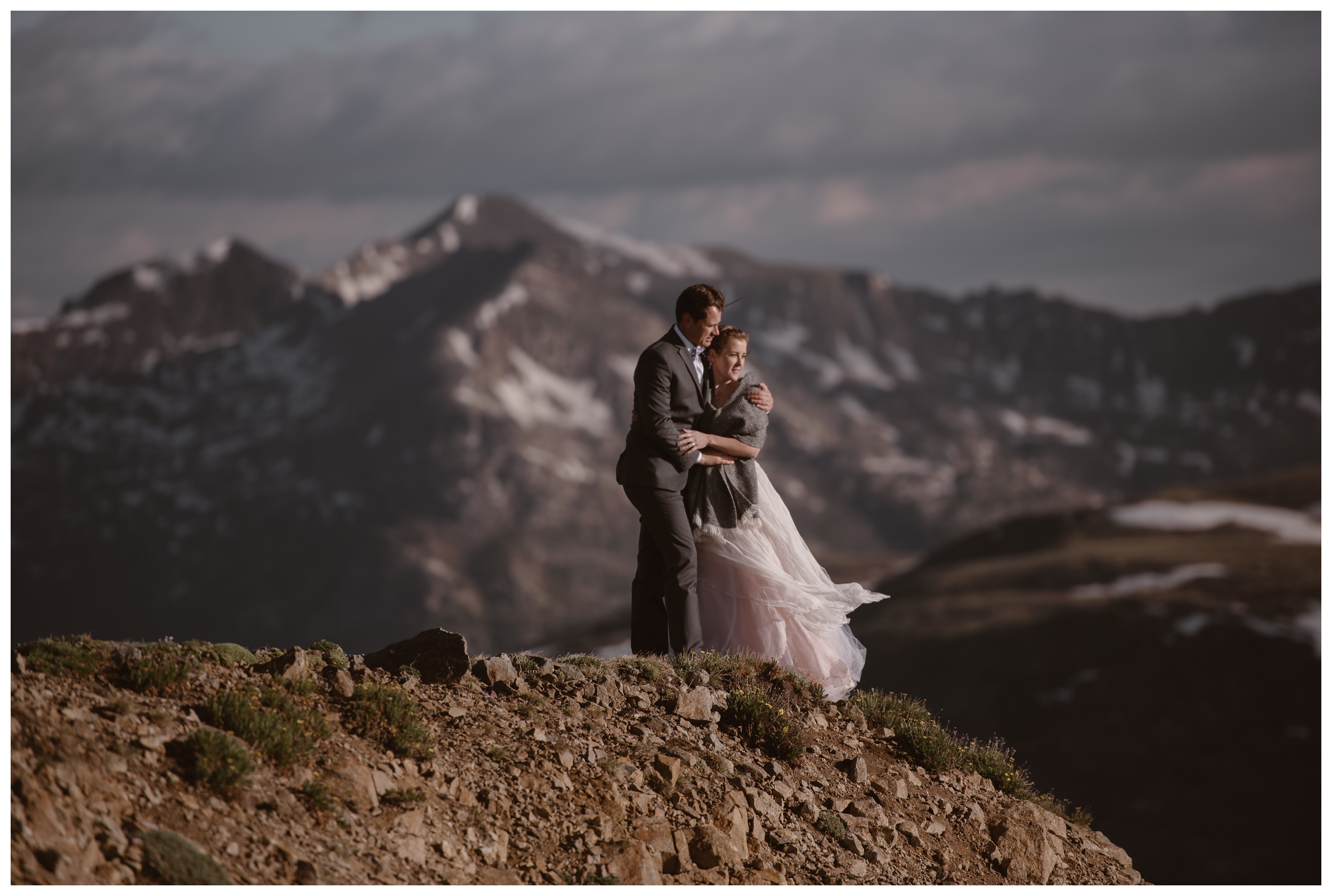 Marcela and Vasily embrace at the top of Independence Pass as the wind blows her blush colored wedding dress following their self solemnizing elopement ceremony. Photo by Maddie Mae, Adventure Instead.