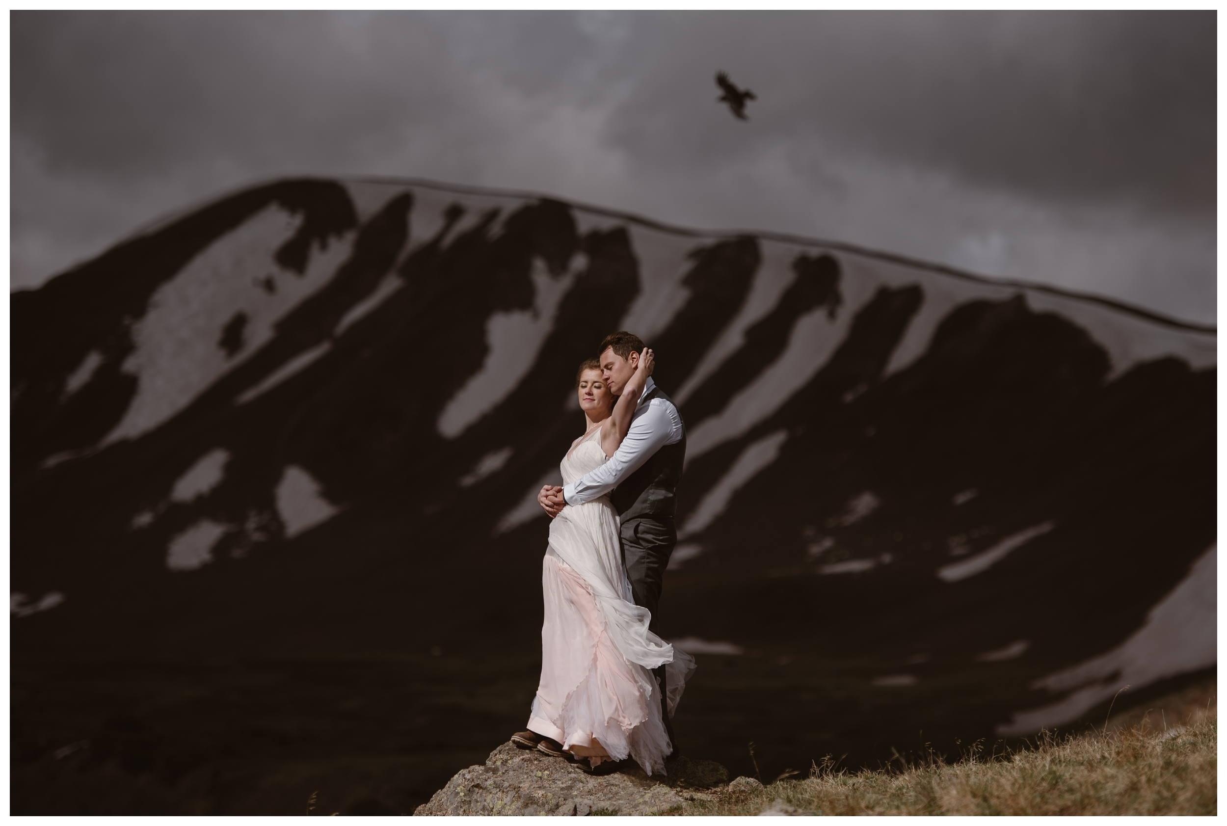 Marcela and Vasily embrace at the top of Independence Pass following their self solemnizing elopement as a bird flies behind them. Photo by Maddie Mae, Adventure Instead.