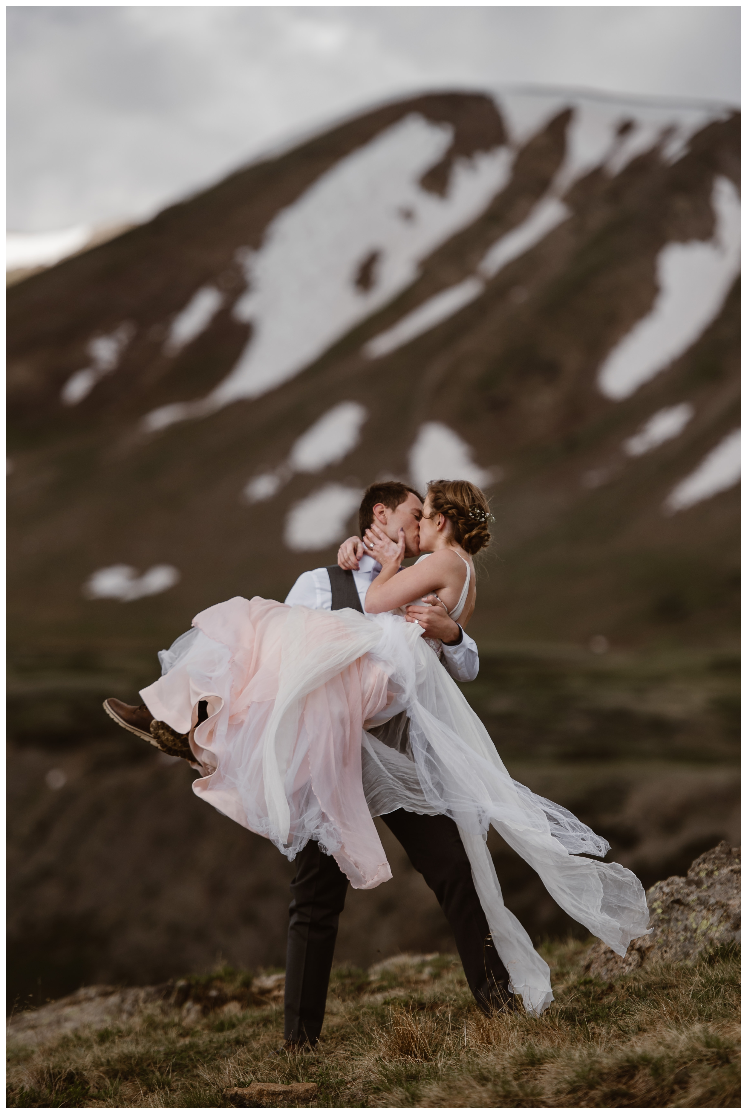 Marcela and Vasily embrace on the top of Independence Pass following their adventurous outdoor sunrise hiking elopement ceremony. Photo by Maddie Mae, Adventure Instead.
