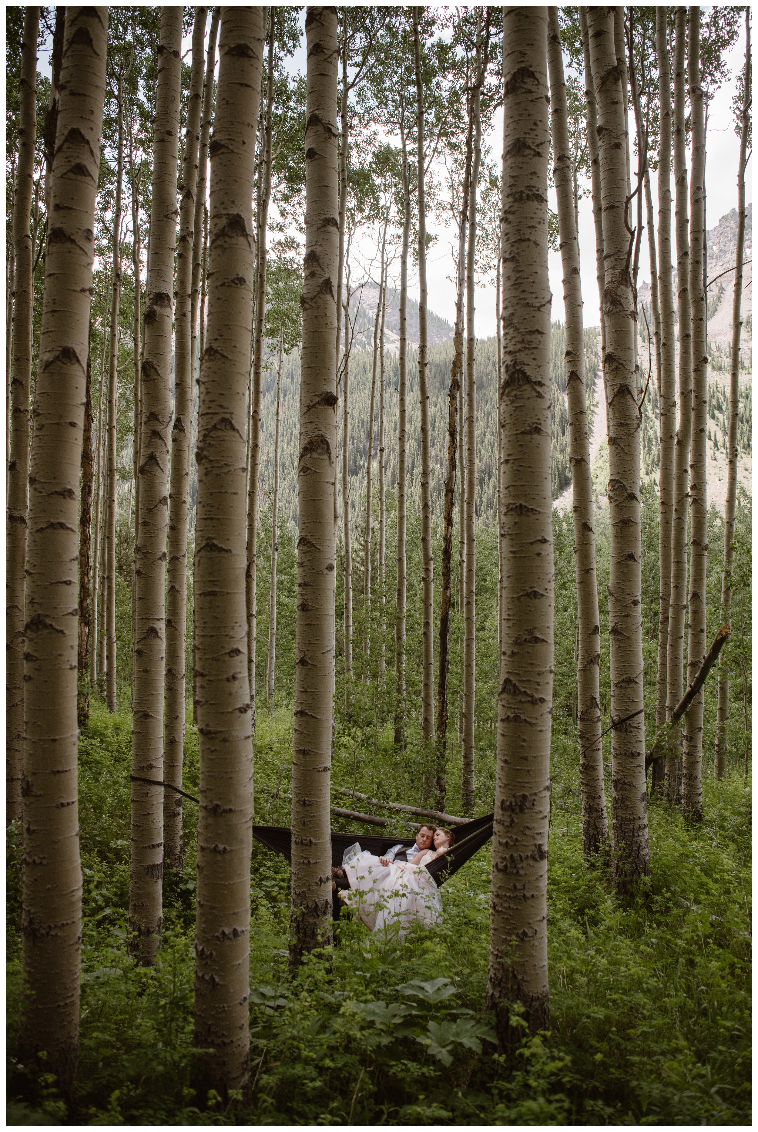 Marcela and Vasily are dwarfed in their pack hammock, hanging between old growth aspen trees outside the Maroon Bells, following their intimate elopement ceremony at the top of Independence Pass. Photo by Maddie Mae, Adventure Instead.