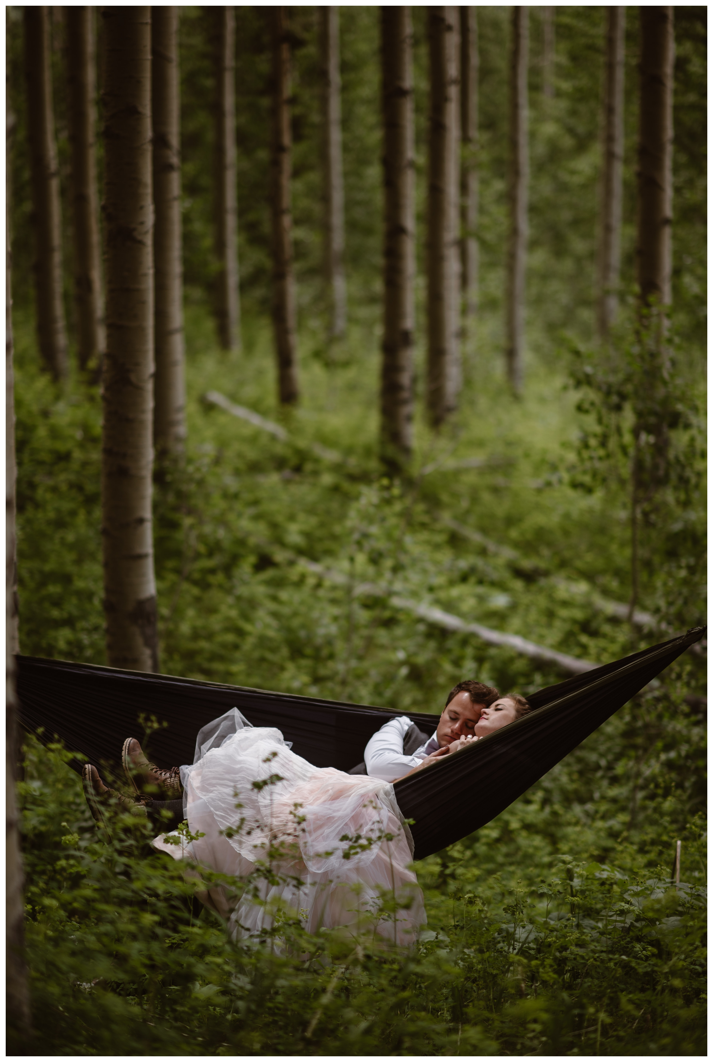 After their sunrise hiking elopement ceremony on the top of Independence Pass, Marcela and Vasily embrace in a hammock strung between two old growth aspen trees. Photo by Maddie Mae, Adventure Instead.