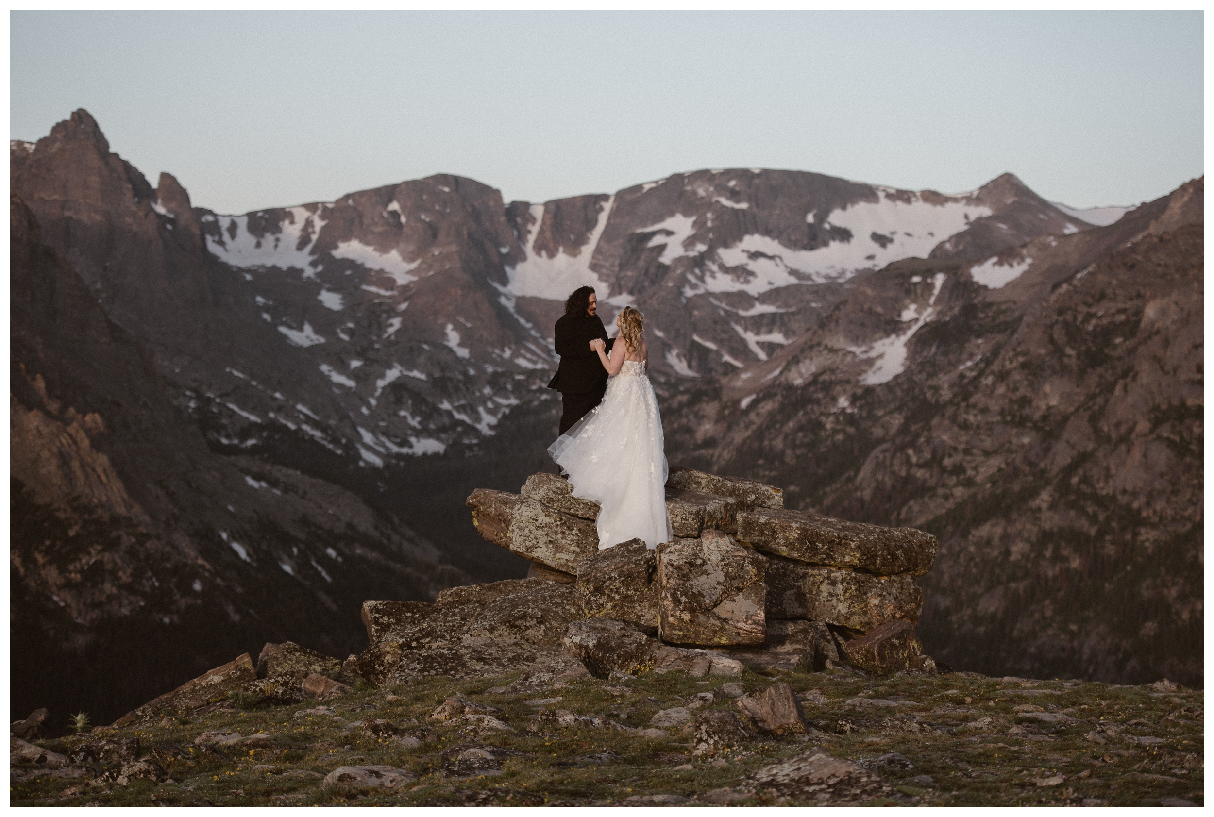 Alicia and Zach embrace at the top of Trail Ridge Road for their first look before their intimate elopement ceremony in Rocky Mountain National Park. Photo by Adventure Instead, Maddie Mae.