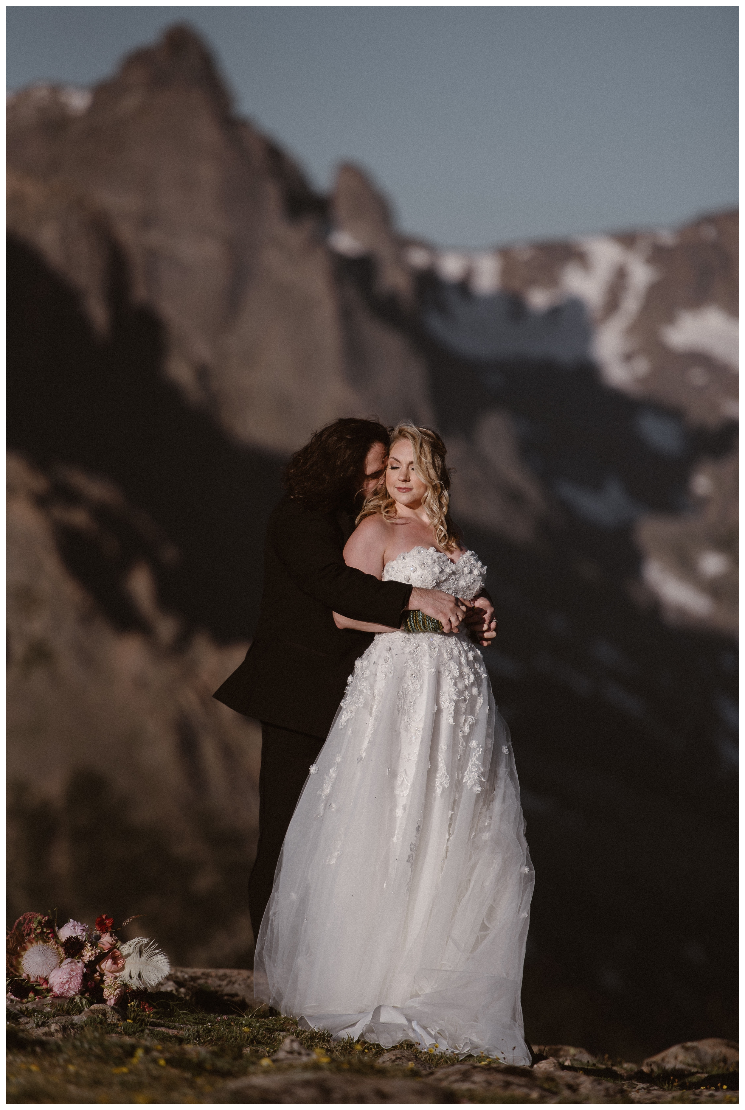 With her bouquet beside them, Alicia and Zach embrace during their first look before their elopement ceremony at 'the most beautiful place they'd ever seen' Trail Ridge Road, Rocky Mountain National Park. Photo by Adventure Instead, Maddie Mae.