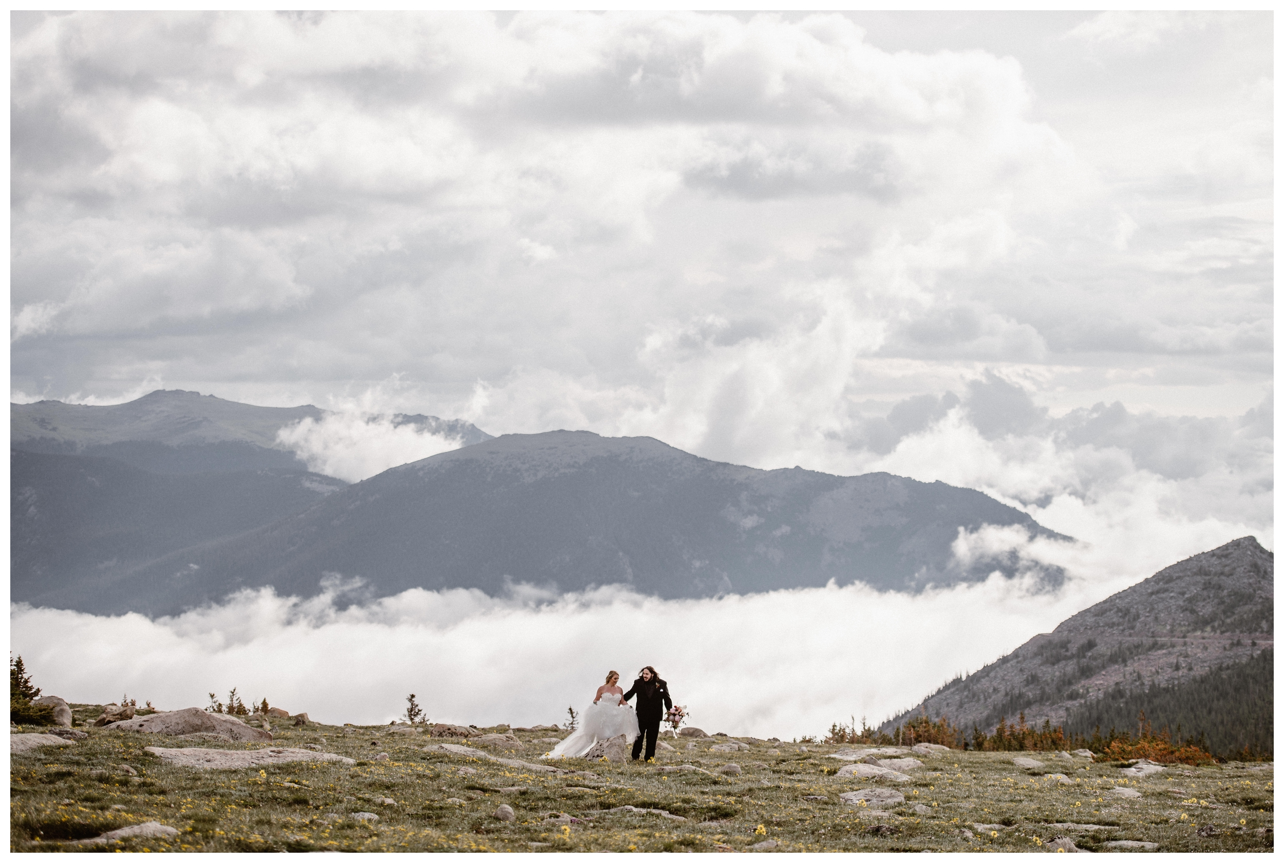 The clouds roll through the valley while Alicia and Zach walk through Trail Ridge Road during their first look before their elopement ceremony in Rocky Mountain National Park. Photo by Adventure Instead, Maddie Mae.
