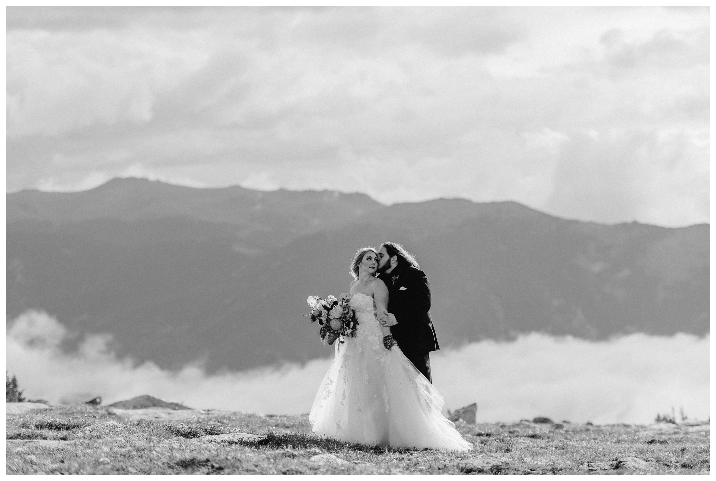 Alicia and Zach embrace while the clouds show off an impressive display of cloud inversion during their first look at Trail Ridge Road in Rocky Mountain National Park. Photo by Adventure Instead, Maddie Mae.