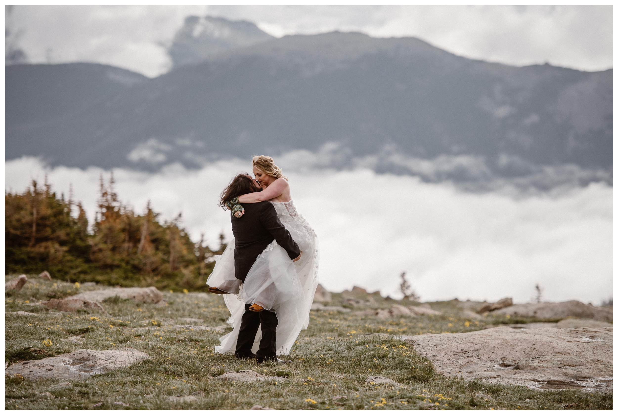 Alicia and Zach embrace at the top of Trail Ridge Road in Rocky Mountain National Park with an impressive display of cloud inversion behind them. Photo by Adventure Instead, Maddie Mae.