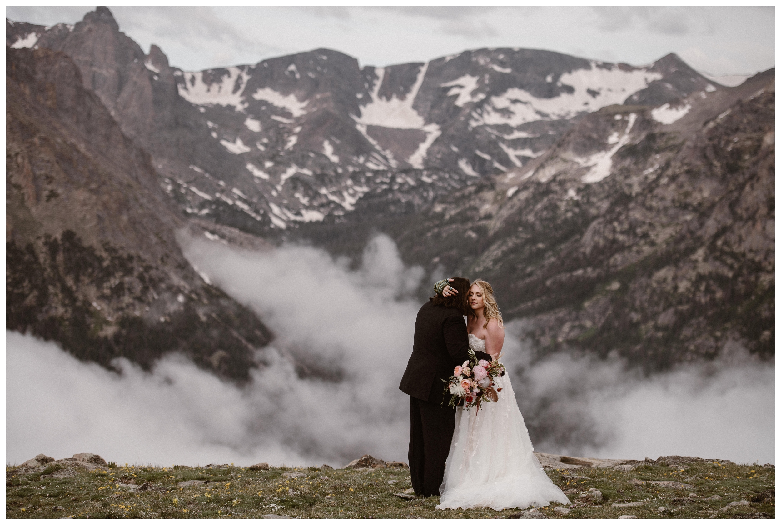 Alicia and Zach embrace at the top of Trail Ridge Road in Rocky Mountain National Park during couple's portraits before their elopement ceremony. Photo by Adventure Instead, Maddie Mae.