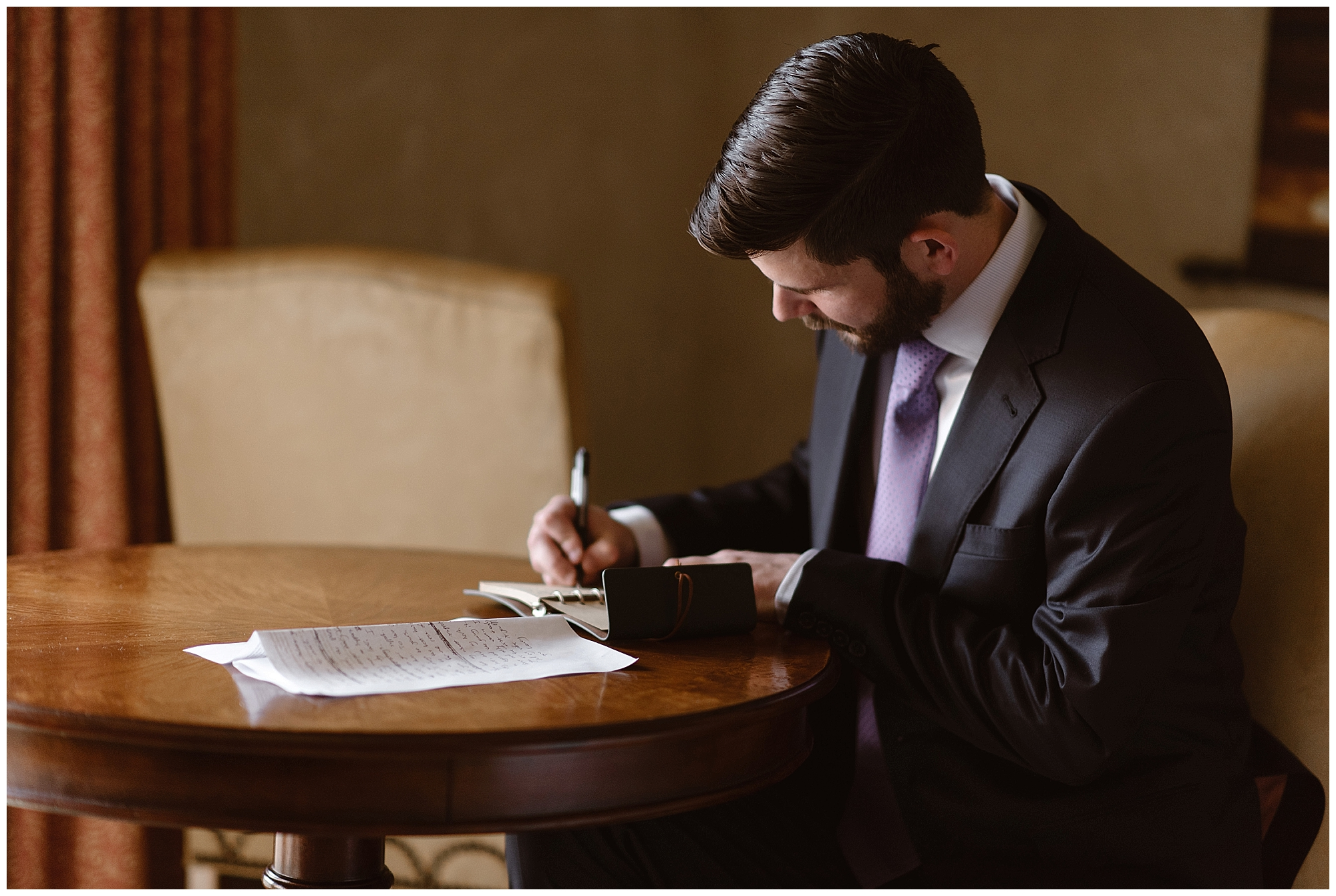 The groom hand writes his vows in a leather bound notebook before his winter elopement ceremony in the Colorado Rocky Mountains. Photo by Adventure Instead, Maddie Mae Elopement Photographers.
