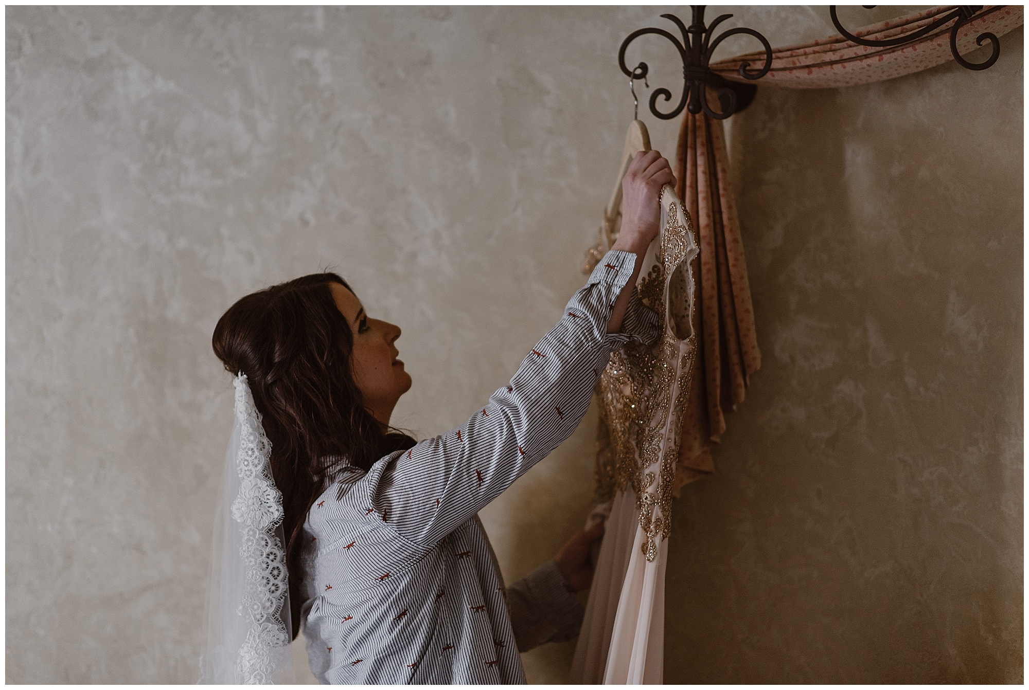 Marlayna picks up her wedding dress while she gets ready for her winter wedding at Sapphire Point near Breckenridge, Colorado. Photo by Adventure Instead, Maddie Mae Elopement Photographers.
