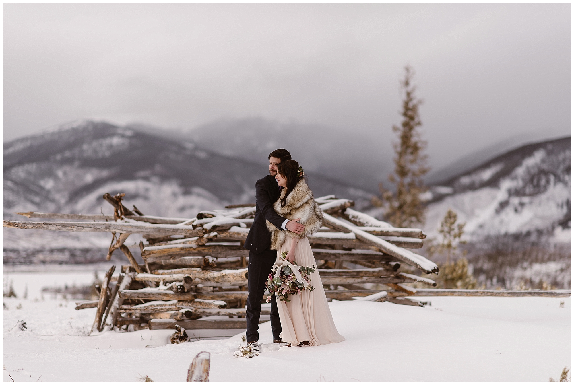 Marlayna and Austin embrace outside in the snow with the Rocky Mountains behind them following their outdoor adventure winter elopement ceremony. Photo by Adventure Instead, Maddie Mae Elopement Photographers.