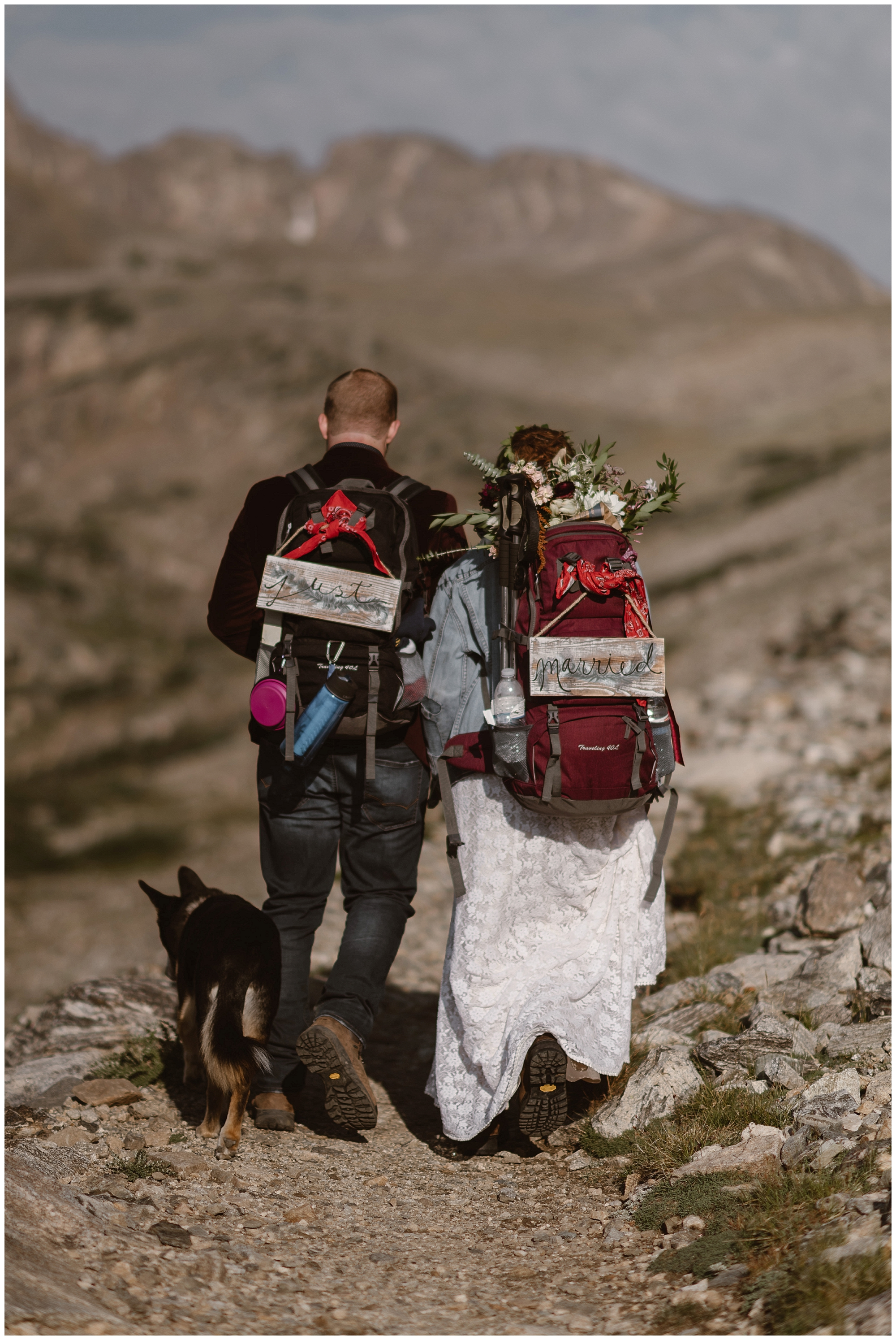 To hike on your elopement day, plan to carry your wedding clothes up and hike down in them. Furry friend and cute customized 'Just Married' signs attached to your hiking backpacks not required. Where you elope and how you say your vows matters! Photo by Maddie Mae, Adventure Instead Elopement Photographers.