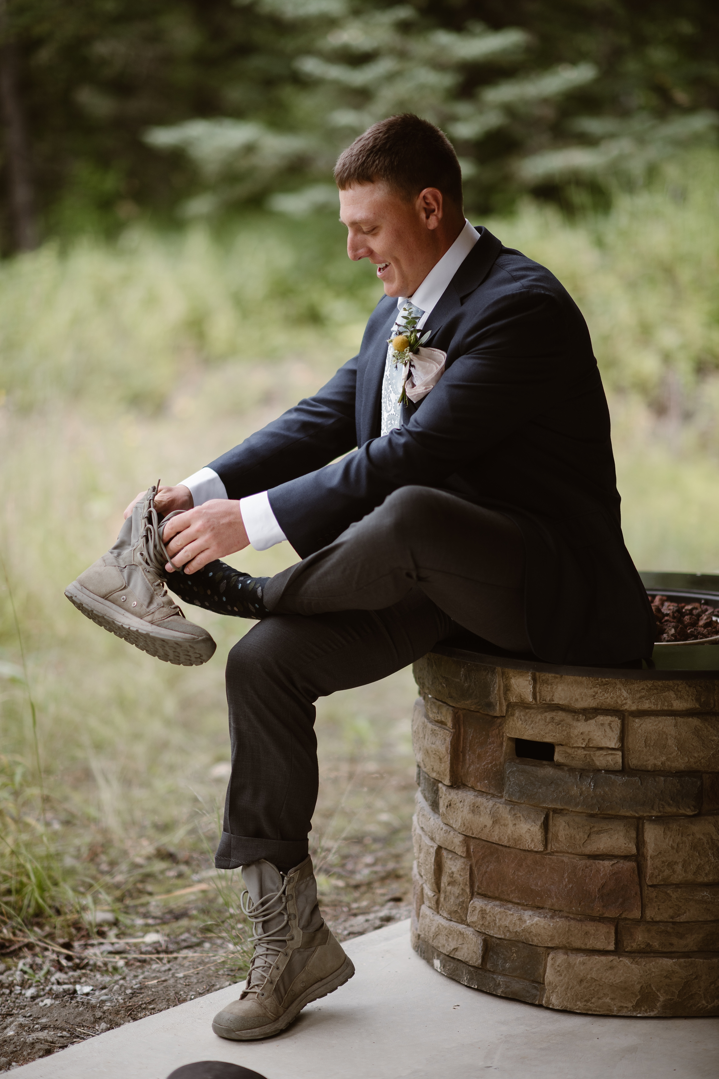 The groom sits on a stone fire pit as he puts on his hiking boots before his Alaska destination wedding. Suited up with his fancy clothes and hiking boots, the groom smiles in this elopement pictures captured by Adventure Instead, an elopement photographer.
