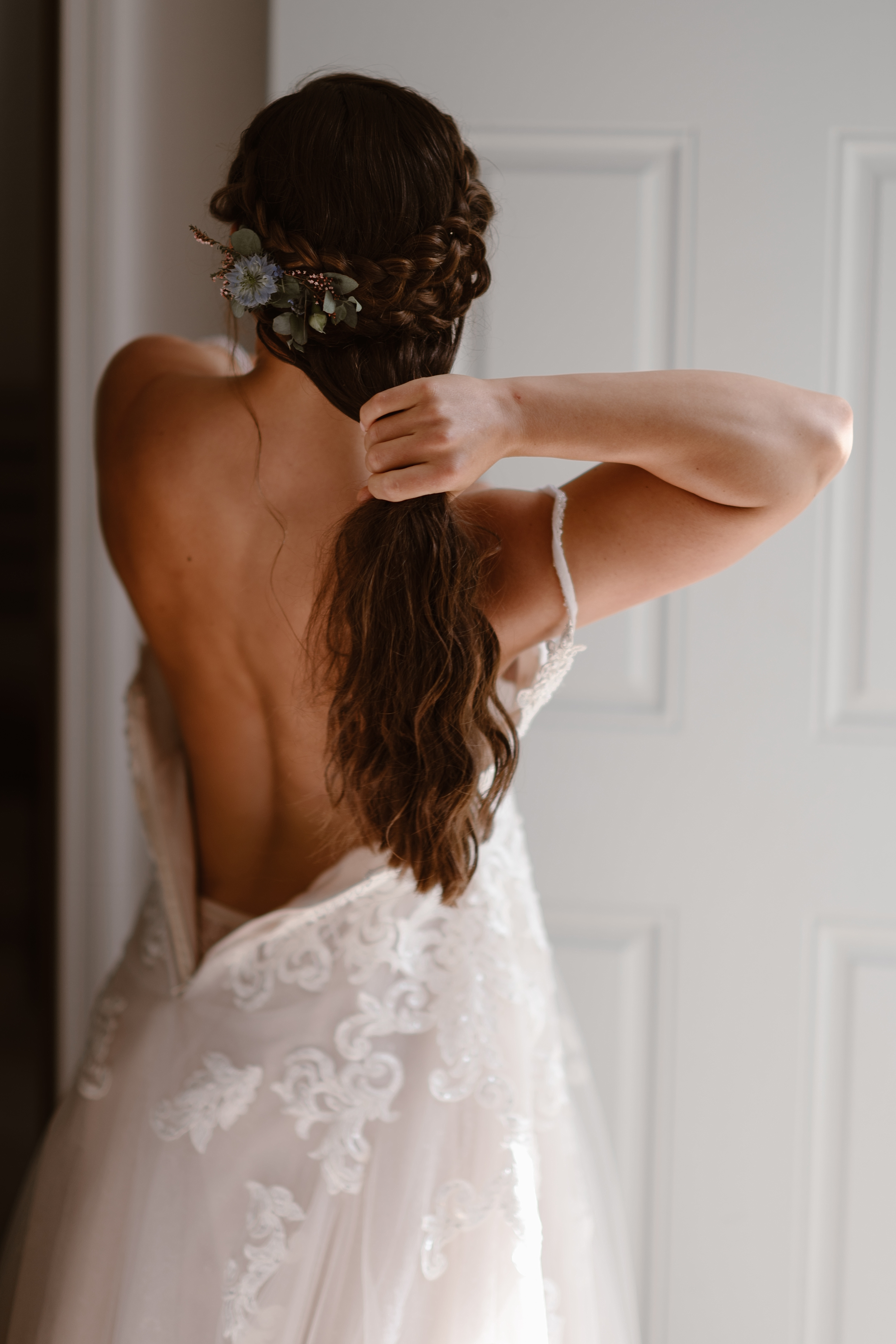 A bride is shown putting on her wedding dress in the doorway of her Airbnb before her Alaska destination wedding. In this photo, captured by elopement photographers Adventure Instead, the bride is shown from the back with her dress halfway zipped, her hand holds her hair away from the zipper displaying a an elaborate braid with flowers.